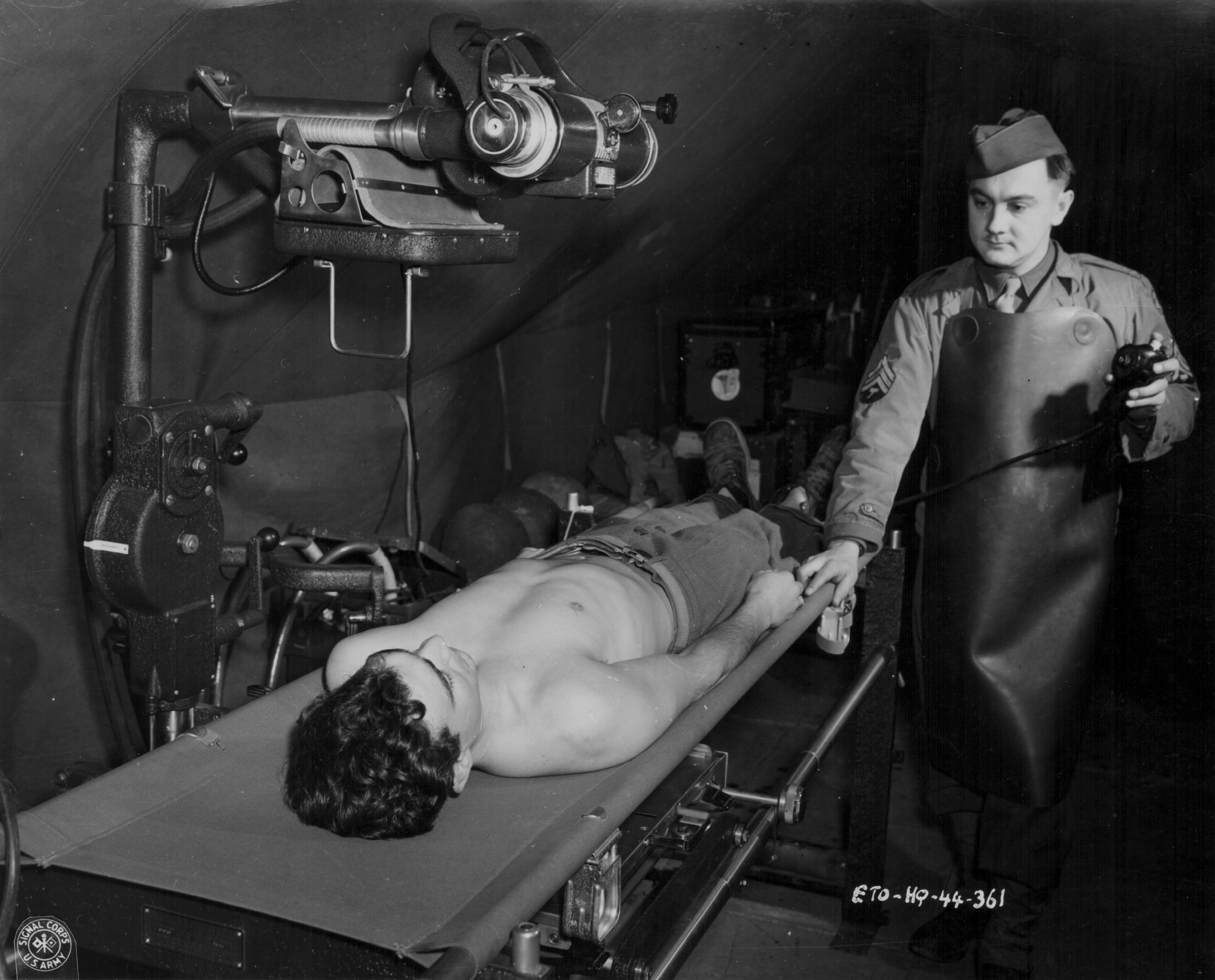 An x-ray technician with the US Medical Corps tending to a wounded soldier during World War Two, circa 1941-1945.