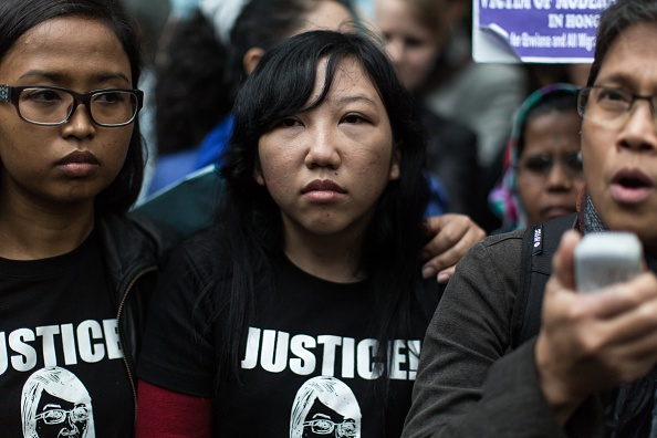 Former Indonesian domestic helper Erwiana Sulistyaningsih, center, looks on as a supporter, right, speaks to the press in front of the District Court following the sentencing of her former employer Law Wan-tung in Hong Kong on Feb. 27, 2015