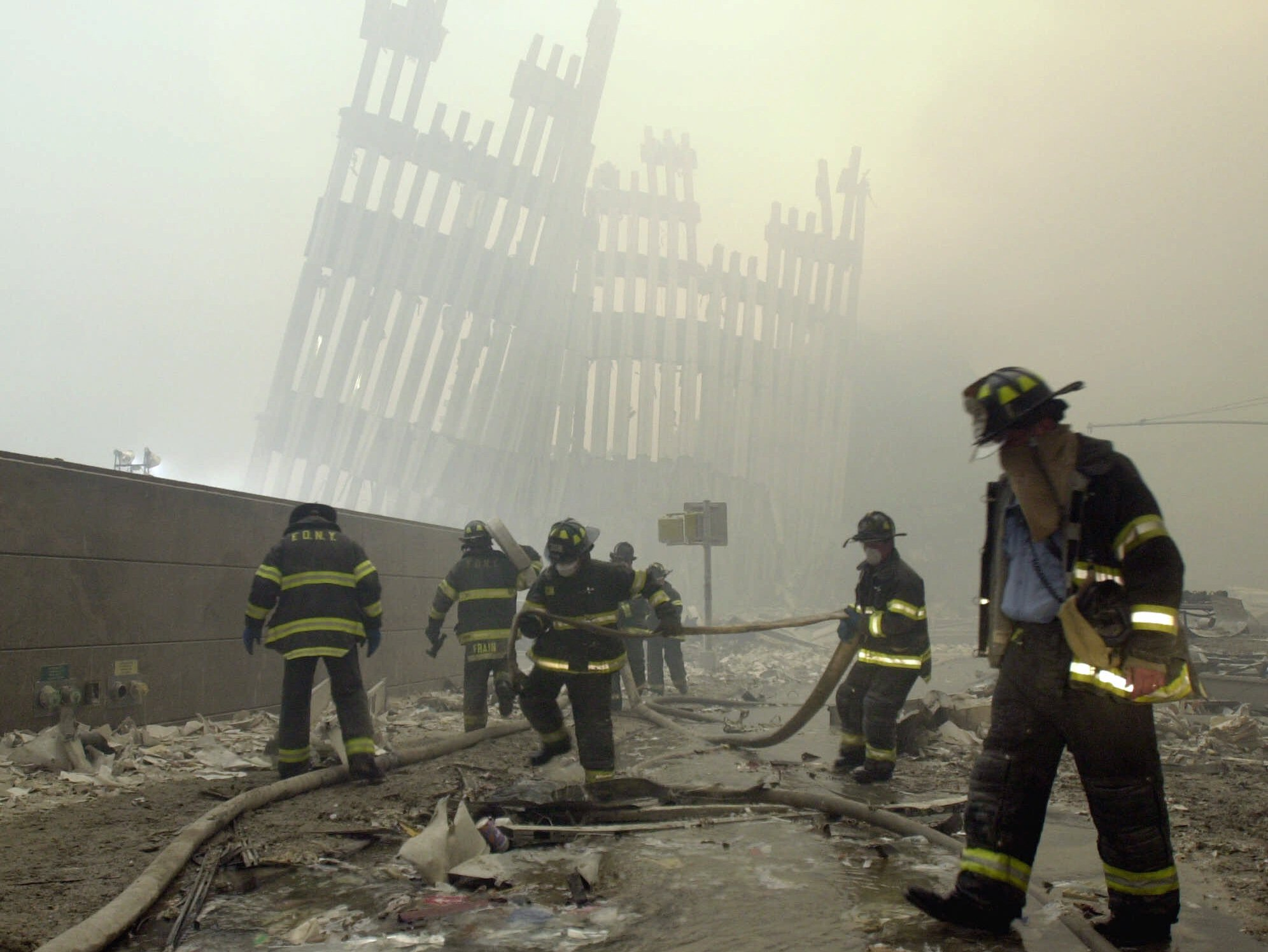 With the skeleton of the World Trade Center twin towers in the background, New York City firefighters work amid debris on Cortlandt St. after Sept. 11, 2001.