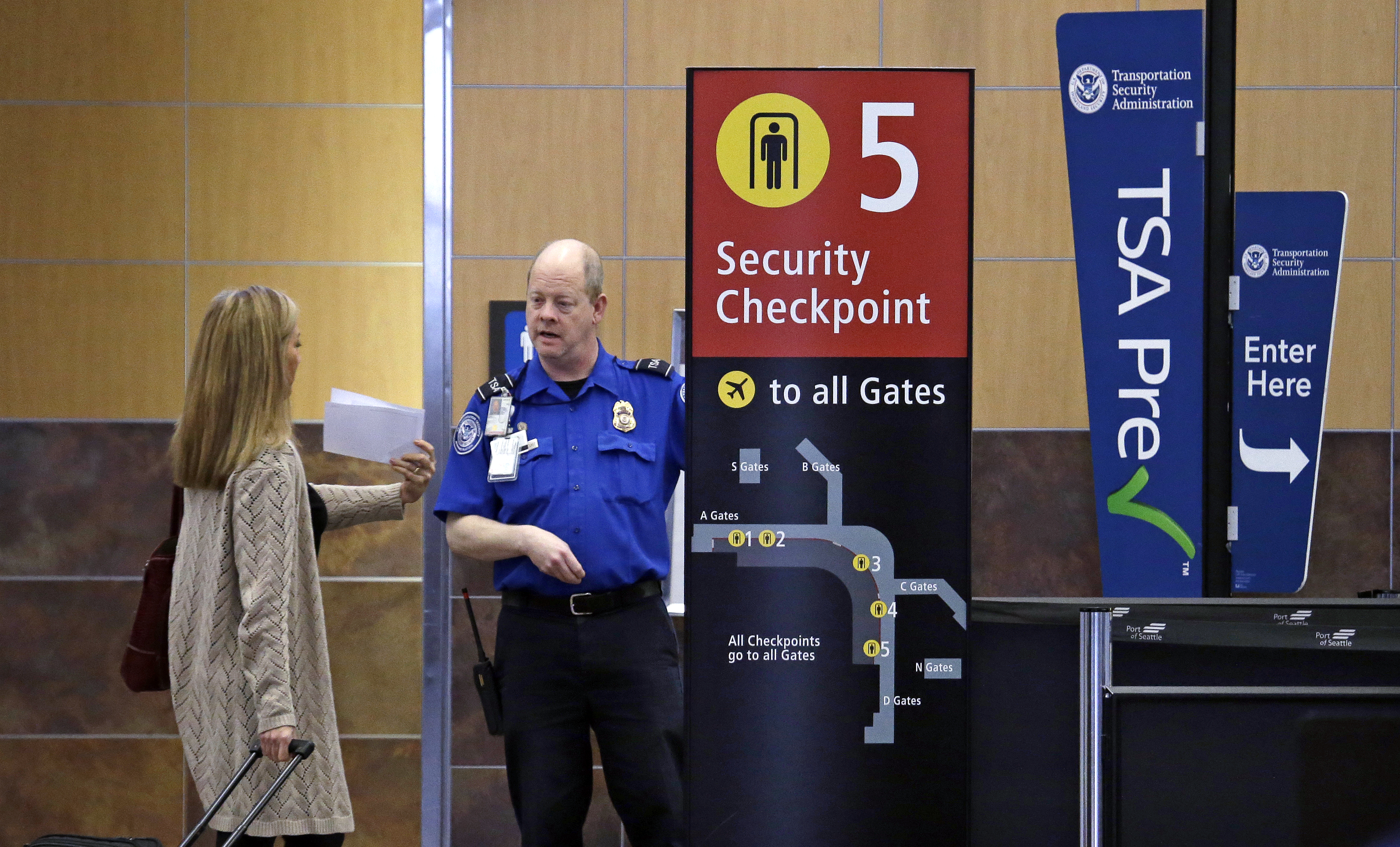 A passenger shows a boarding pass to a TSA agent at a security check-point at Seattle-Tacoma International Airport in SeaTac, Wash, March 24, 2015.