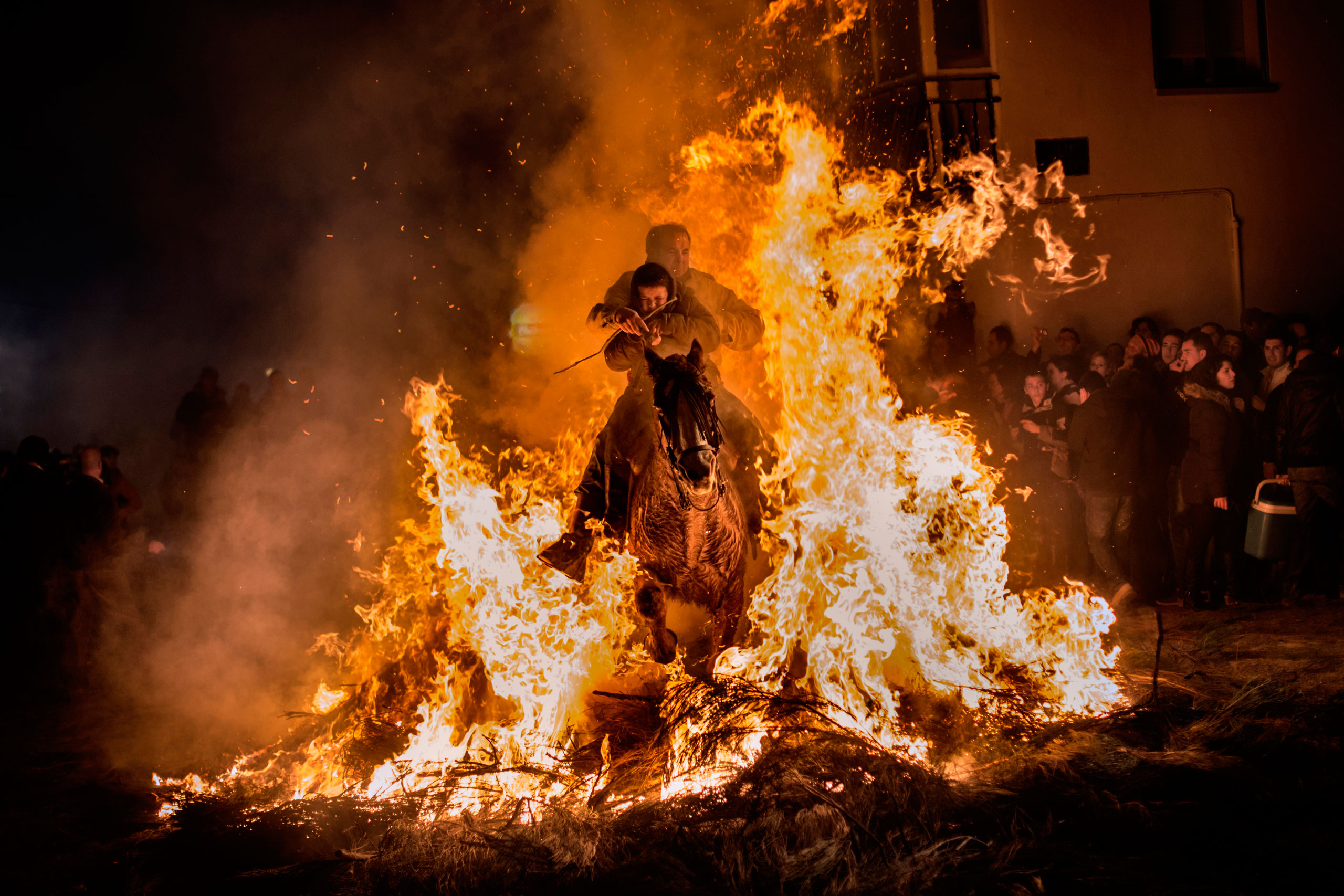 A man rides a horse with a child through the flames during the  Luminarias  annual religious celebration on the night before Saint Anthony's, patron of animals, in the village of San Bartolome de los Pinares, about 62 miles northwest of Madrid, Spain, Jan. 16, 2014. According to tradition that dates back 500 years, people ride their horses through the narrow cobblestone streets of this small village to purify the animals with the smoke of the bonfires.