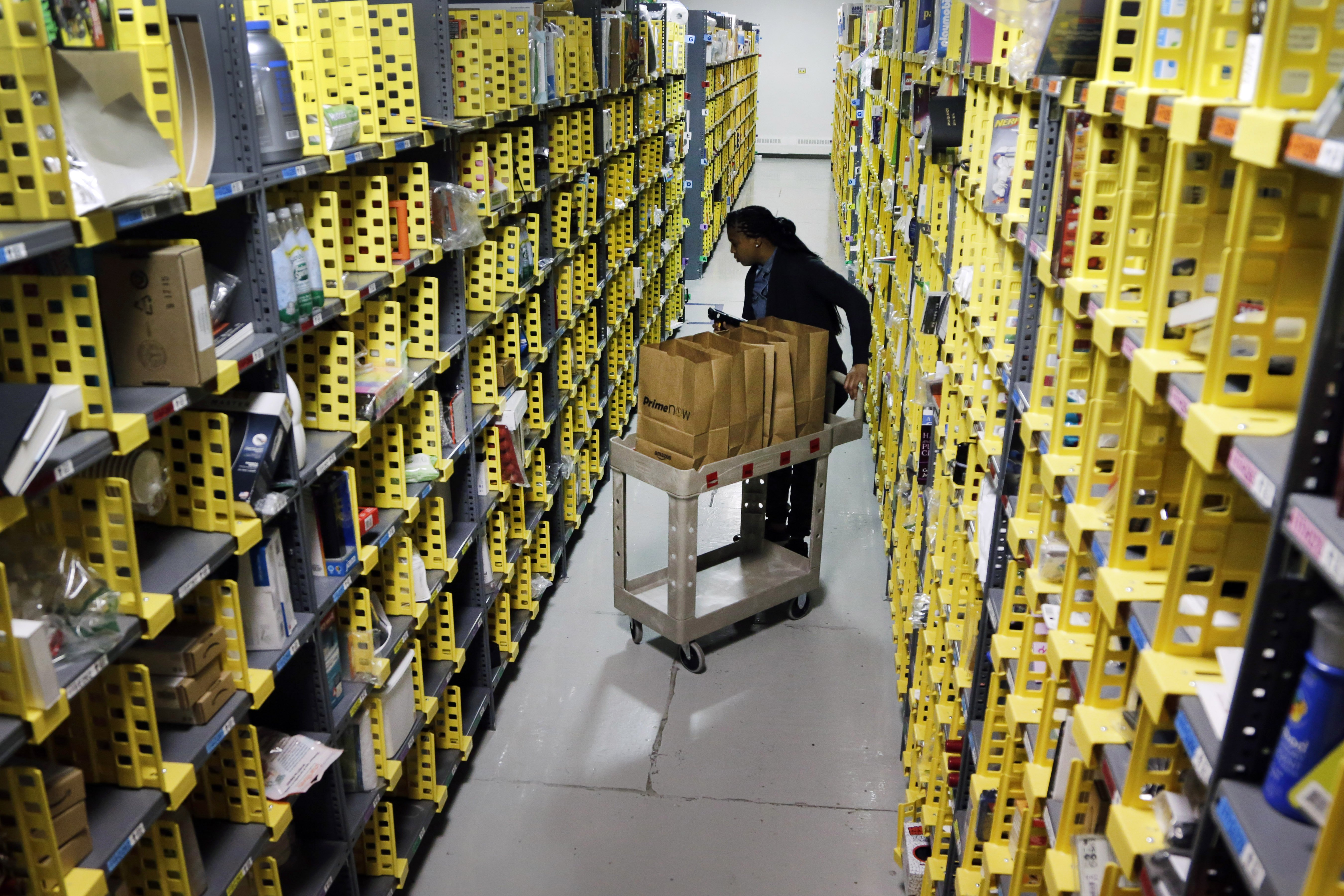 Amazon Prime employee Alicia Jackson hunts for items at the company's urban fulfillment facility that have been ordered by customers on Dec. 22, 2015, in New York.