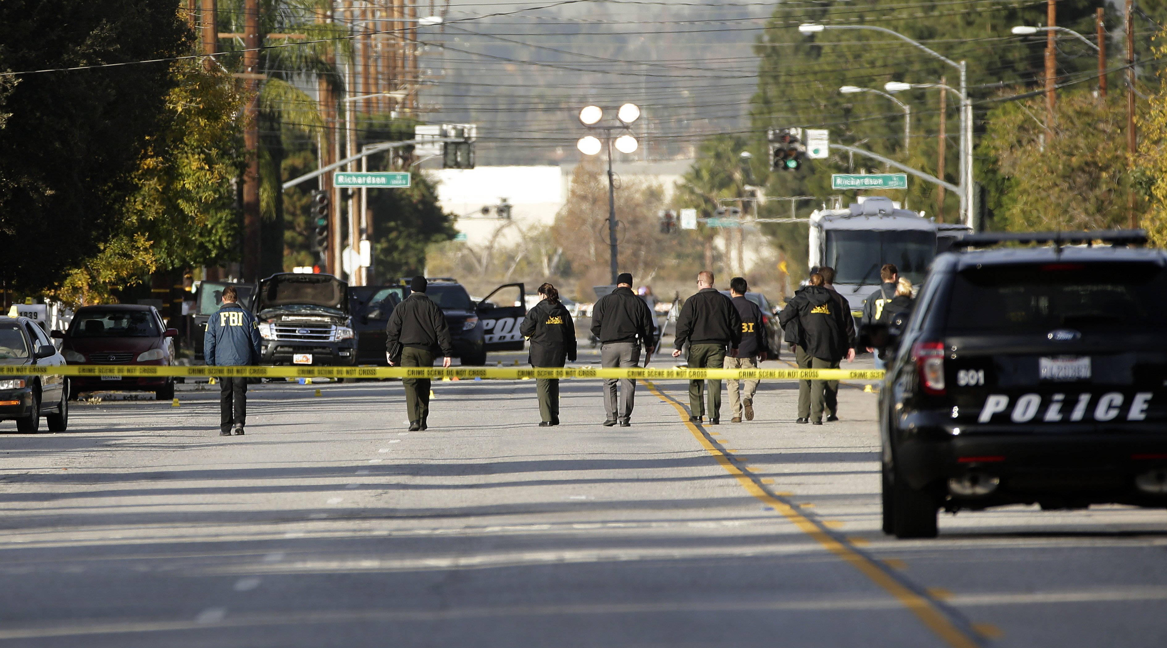 Investigators search for bullet casings at the scene where Wednesday's police shootout with suspects took place in San Bernardino, Calif on Dec. 3, 2015.