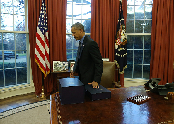 US President Barack Obama gets up from his desk after signing the budget bill that will fund the government until next September, in the Oval Office at the White House December 18, 2015 in Washington, DC.