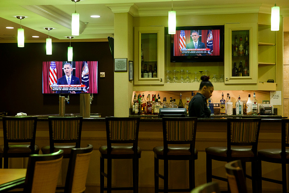 A bartender at a hotel near the Inland Regional Center  watches President Obama speak on TV during the aftermath of a mass shooting that killed 14 people on Sunday, December 6, 2015 in San Bernardino, California.