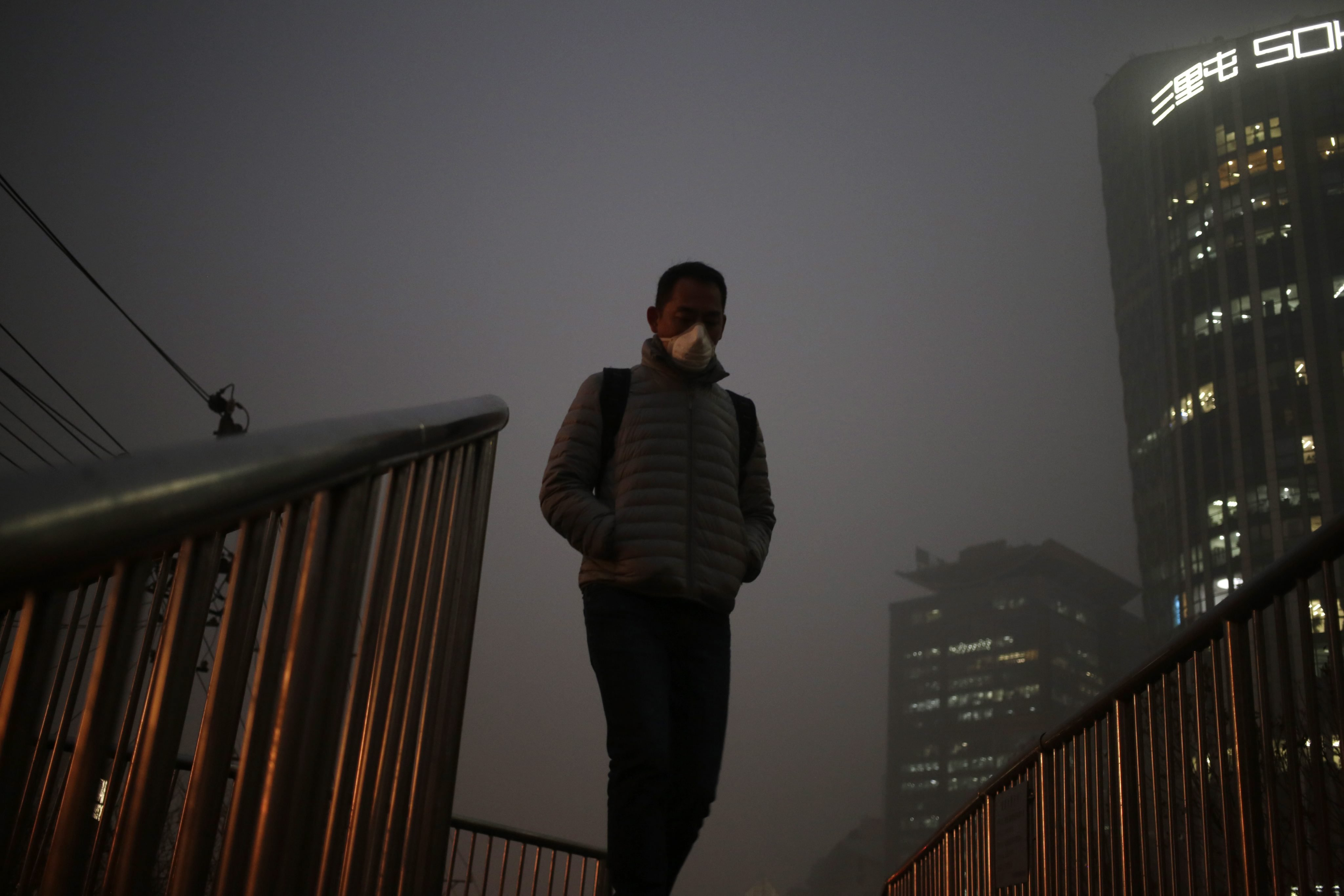 A man wears a mask as he walks on a bridge shrouded in smog in Beijing, Dec. 1, 2015. Beijing issued its second red alert for smog on Dec. 18, 2015, urging schools to close and residents to stay indoors for the second time in 10 days.