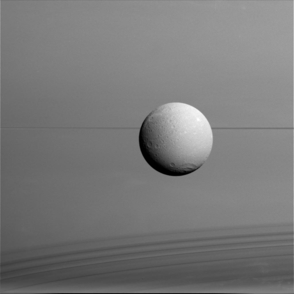 The Saturnian moon Dione hangs in front of Saturn and its icy rings in this view, captured during the Cassini spacecraft's final close flyby of the icy moon on Aug. 17, 2015.