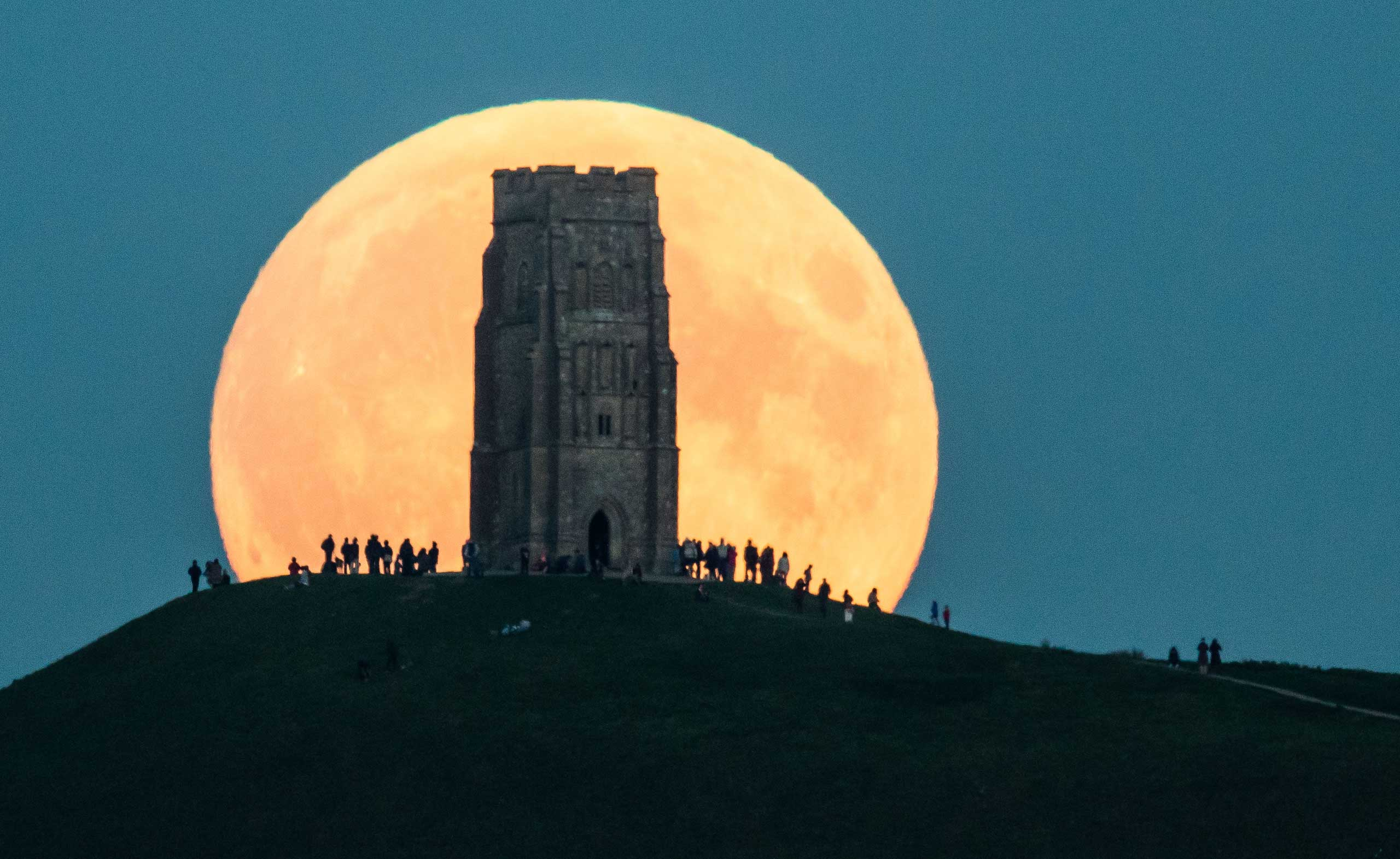 The supermoon rises behind Glastonbury Tor on Sept. 27, 2015 in Glastonbury, England. A supermoon occurs when the moon is both full and at the closest approach it makes to Earth during its orbit.