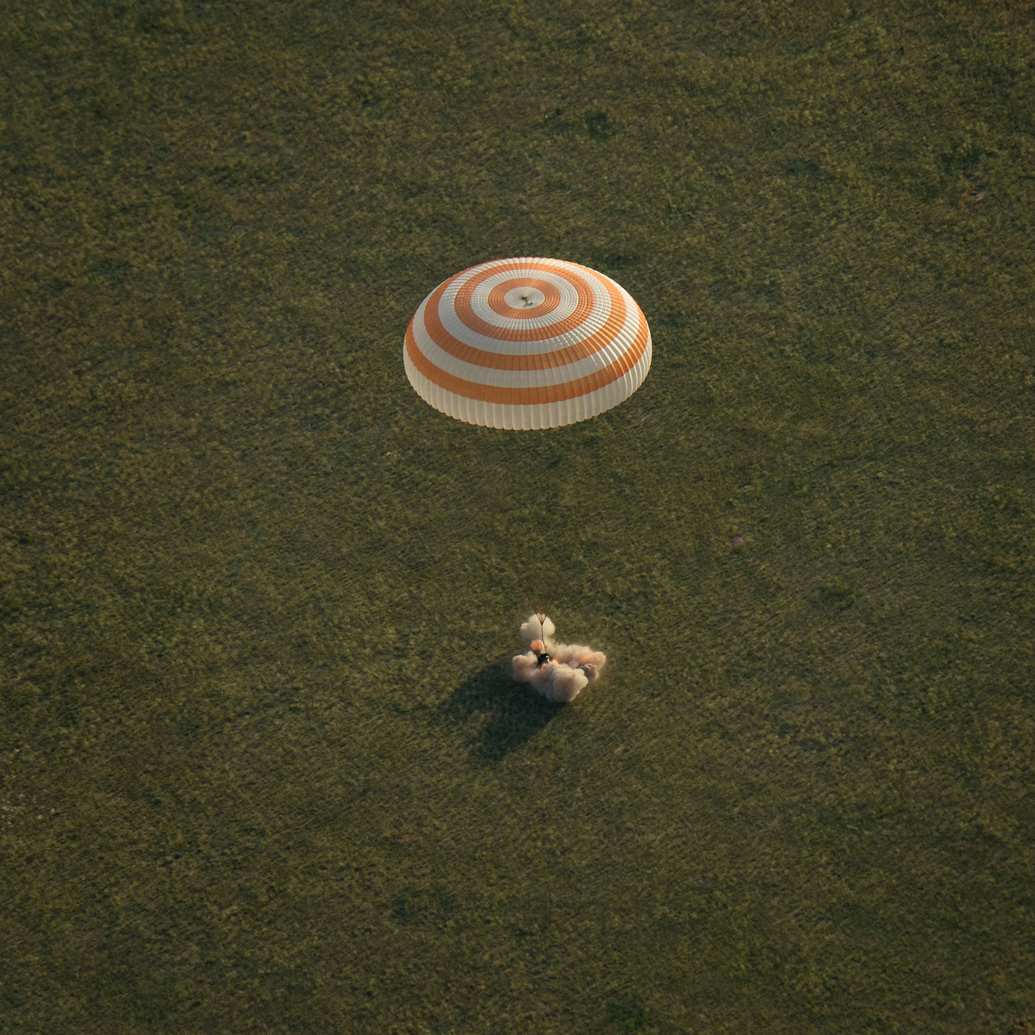 A Soyuz spacecraft returning from the International Space Station lands in Kazakhstan on June 11, 2015, with NASA astronaut Terry Virts, Russian cosmonaut Anton Shkaplerov, and Italian astronaut Samantha Cristoforetti of the European Space Agency aboard. The burst of fire and smoke at the point of impact comes from the braking rockets the Soyuz fires to ease the landing.