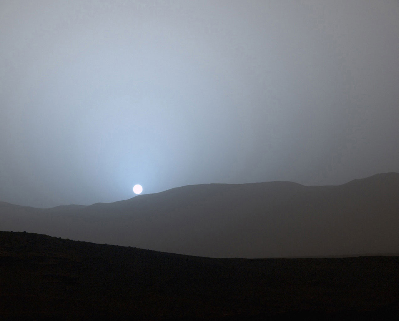 NASA's Curiosity Mars rover recorded this view of the sun setting at the close of the mission's 956th Martian day, or sol, on April 15, 2015, from the rover's location in Gale Crater.  This was the first sunset observed in color by Curiosity.