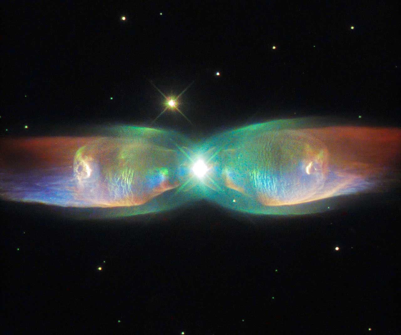 The Twin Jet Nebula, or PN M2-9, is a striking example of a bipolar planetary nebula, formed when the central object is not a single star, but a binary system.  An earlier image of the Twin Jet Nebula using data gathered by Hubble's Wide Field Planetary Camera 2 was released in 1997. This newer version released on Aug. 26, 2015 incorporates more recent observations from the telescope's Space Telescope Imaging Spectrograph.