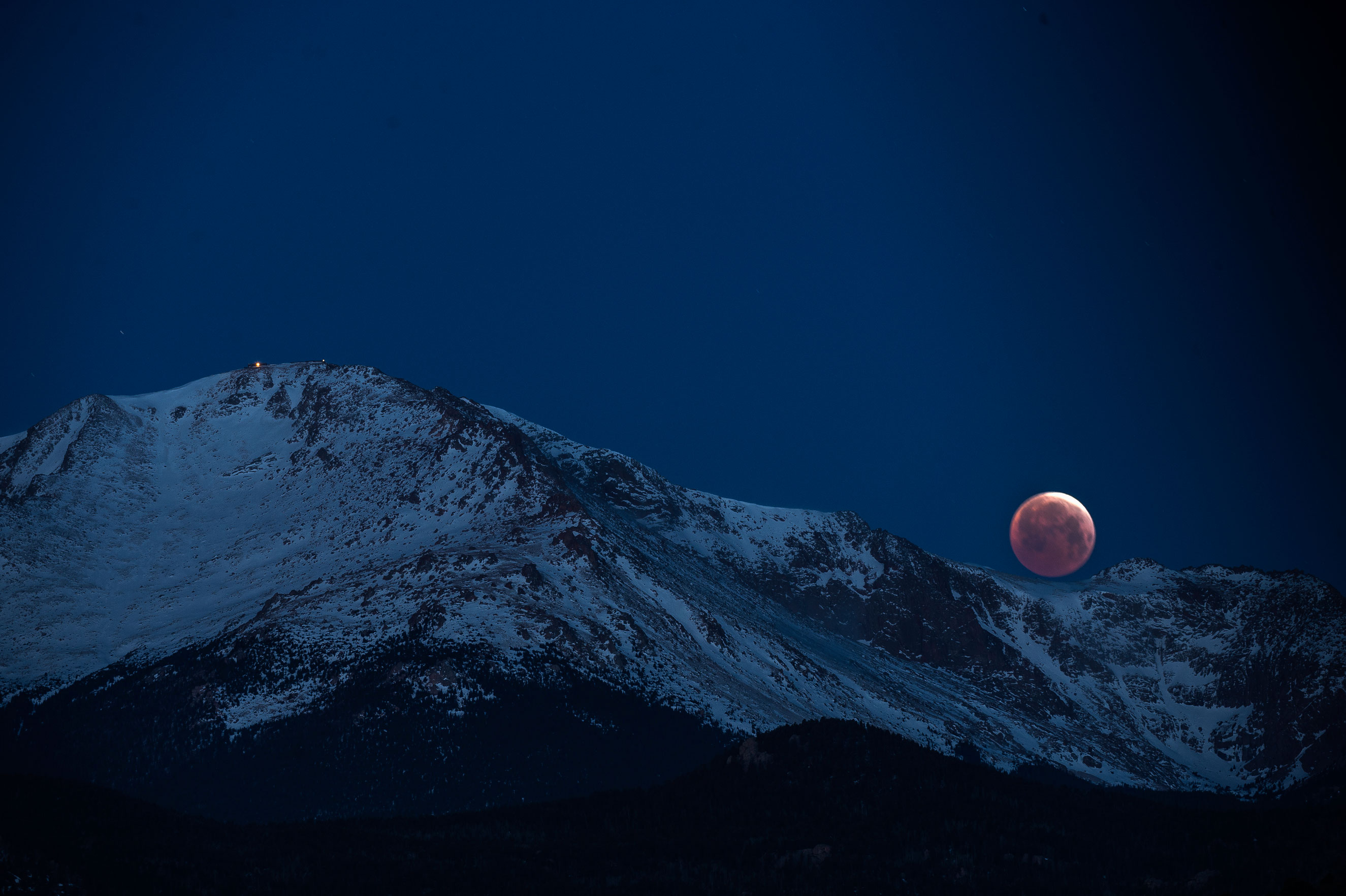 The blood moon lunar eclipse sets behind Pikes Peak on April 4, 2015 in Colorado Springs. The reddish hue is the result of Earth moving between the sun and the moon and Earth's atmosphere absorbing blue wavelengths and allowing red ones to pass through.