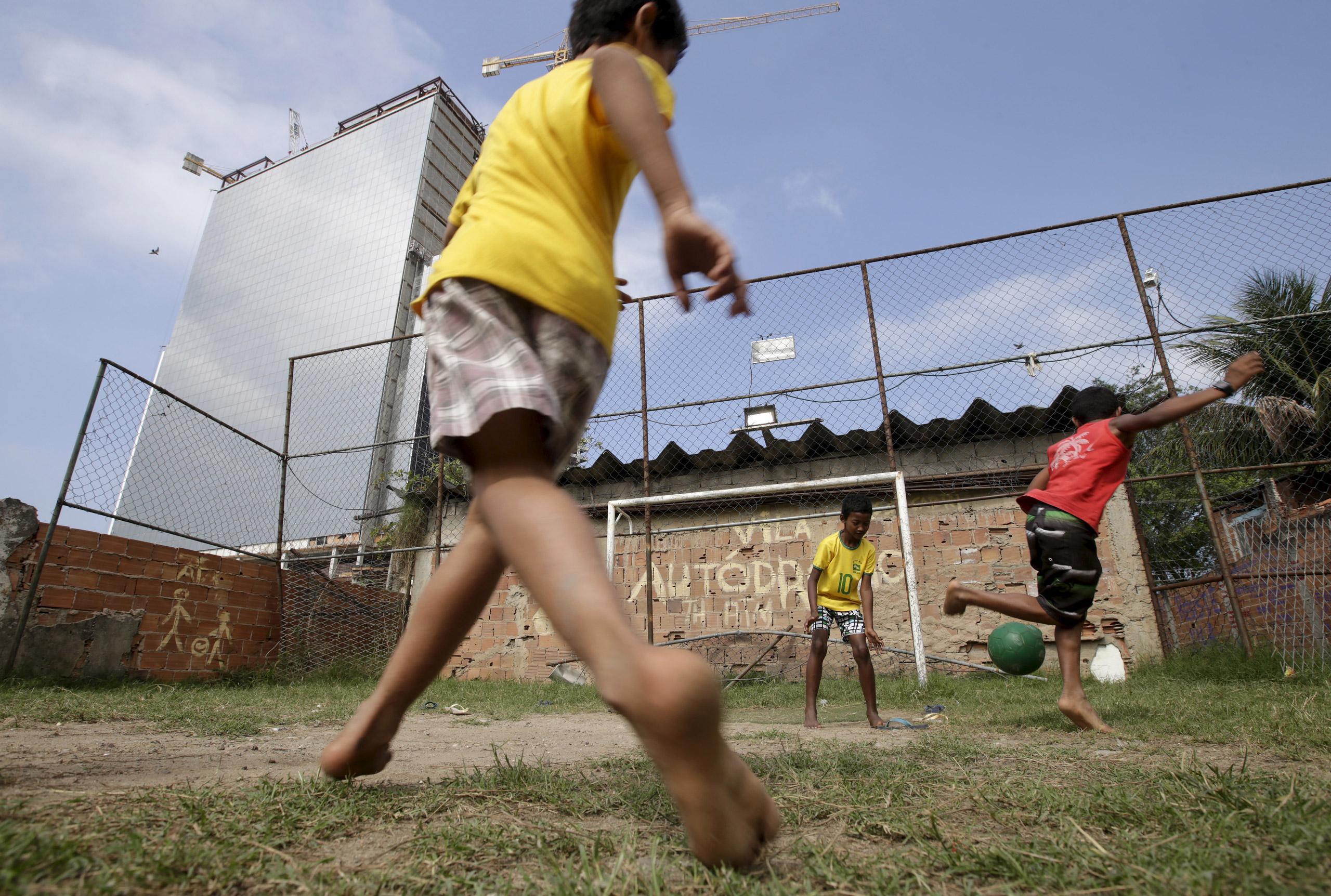 Children play soccer in the Vila Autodromo slum in Rio de Janeiro on July 28, 2015.