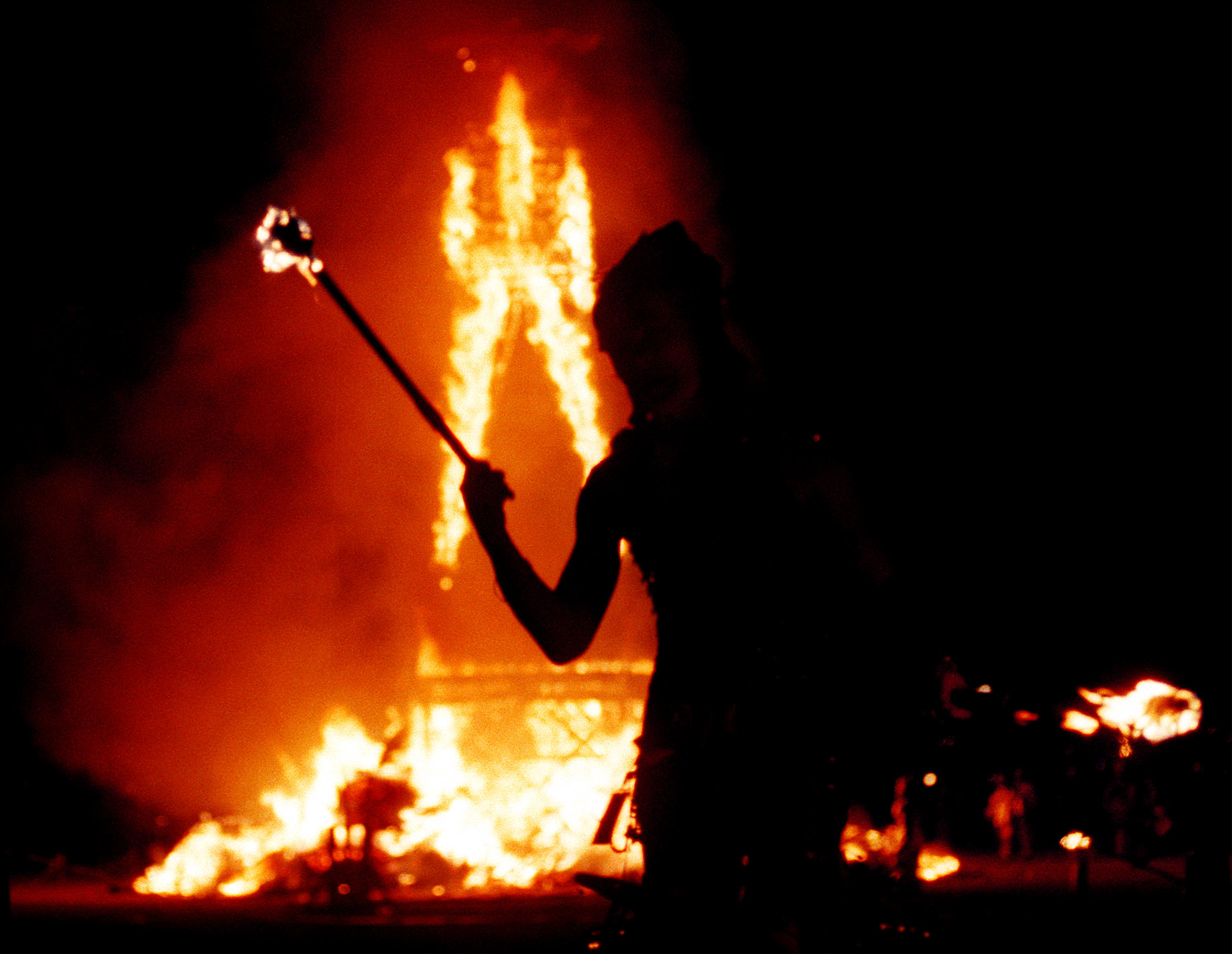 A dancer juggles fire as a 52-foot tall wooden man as it goes up in flames September 2, 2000 during the15th annual Burning Man festival in the Black Rock Desert near Gerlach, Nevada.