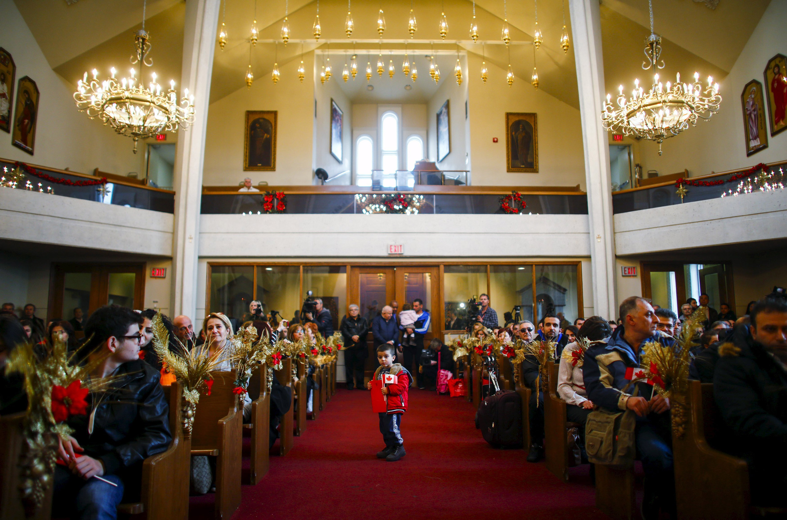 Syrian refugee Levon Kourken, 4, stands on an aisle during a welcoming service for Syrian refugees at St. Mary Armenian Apostolic Church in Toronto on Dec. 11, 2015.