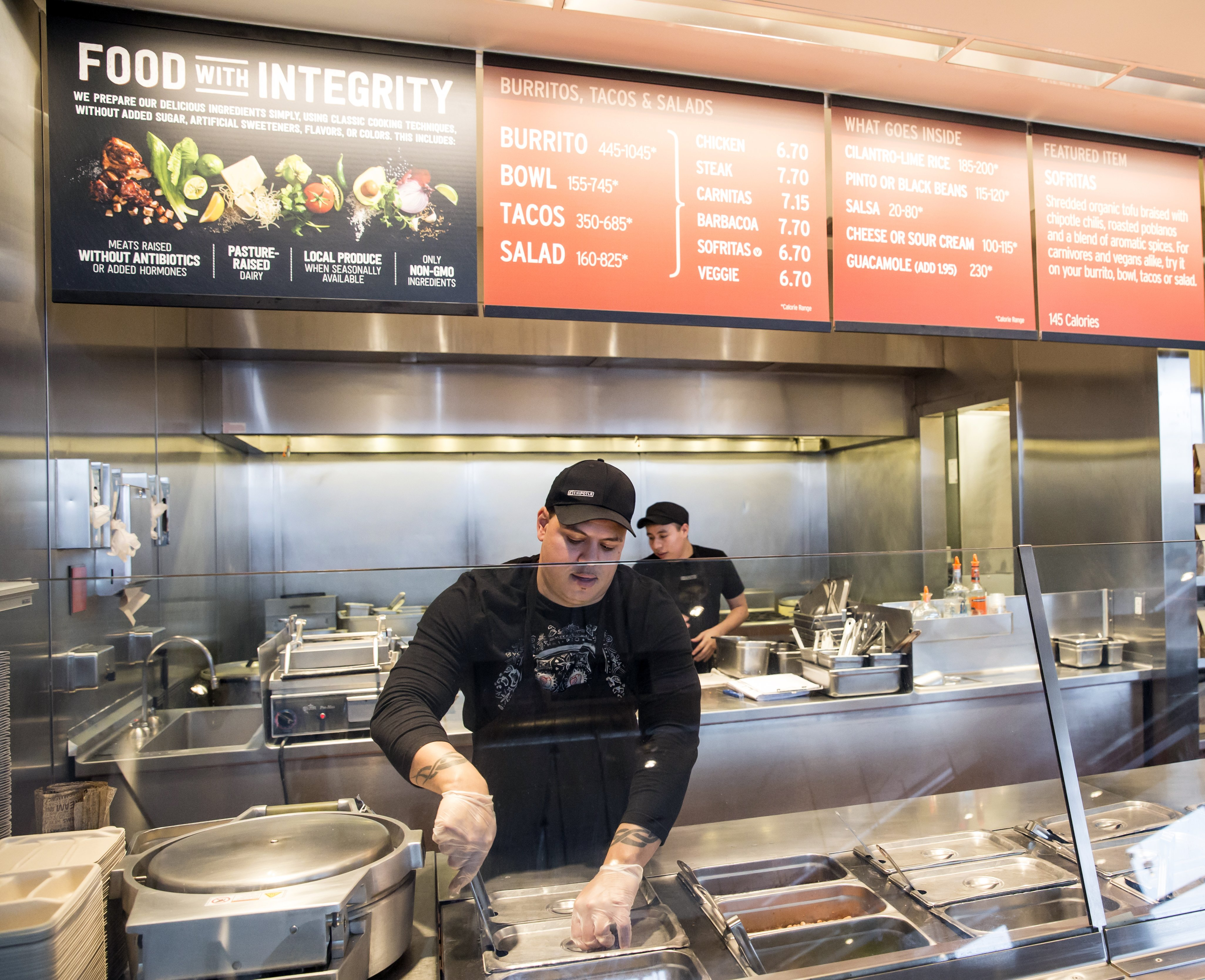 FILE - In this Dec. 15, 2015, file photo, a Chipotle Mexican Grill employee prepares food, in Seattle. After an E. coli outbreak that sickened more than 50 people, Chipotle is changing its cooking methods to prevent the nightmare situation from happening again. (AP Photo/Stephen Brashear, File)
