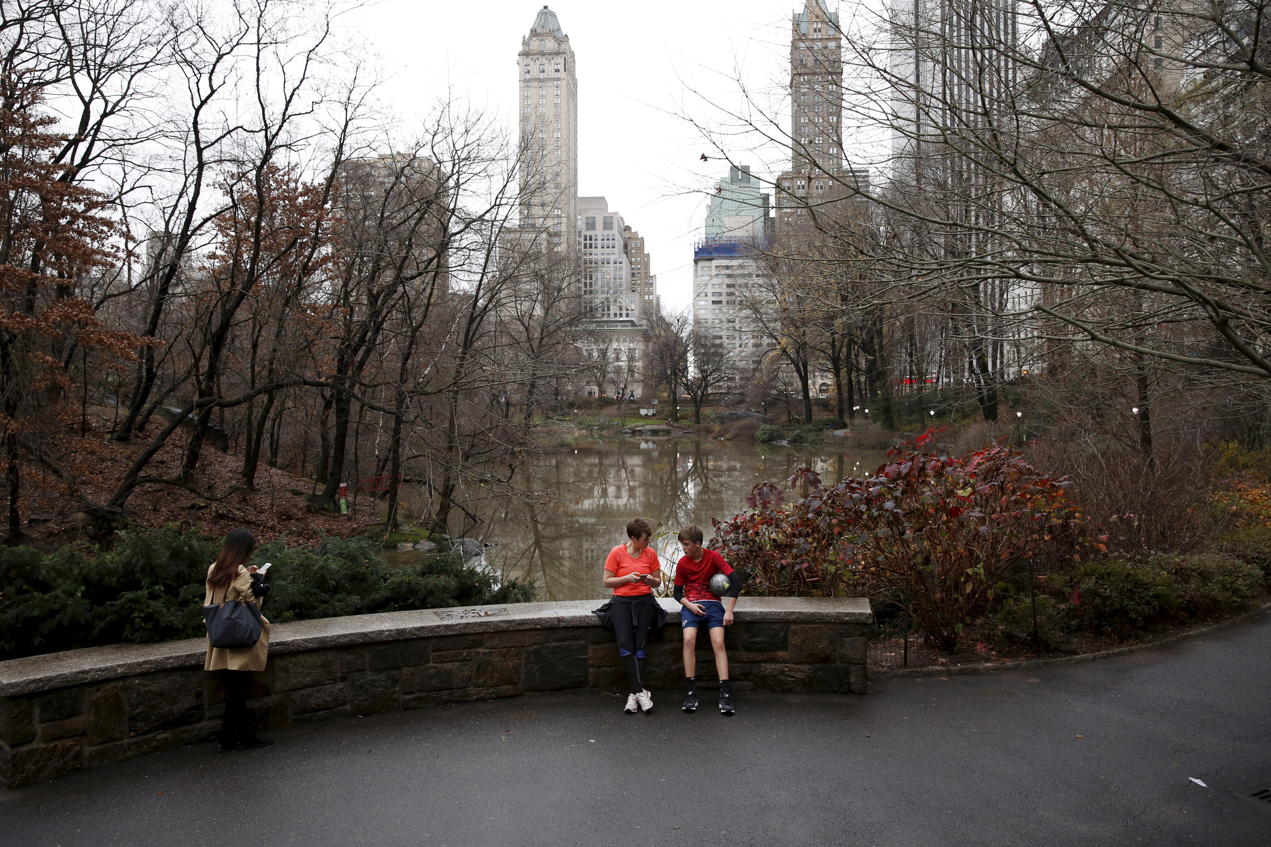 People sit to rest in Central Park during an unseasonably warm day in New York on Dec.24, 2015.