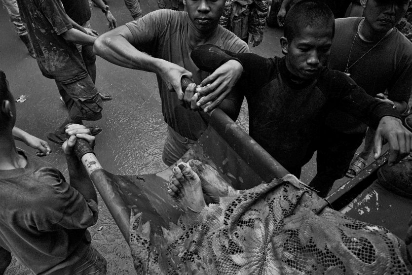 Philippine Army soldiers carry the body of a victim trapped by floodwaters in the eastern part of Metro Manila in September 2009.
