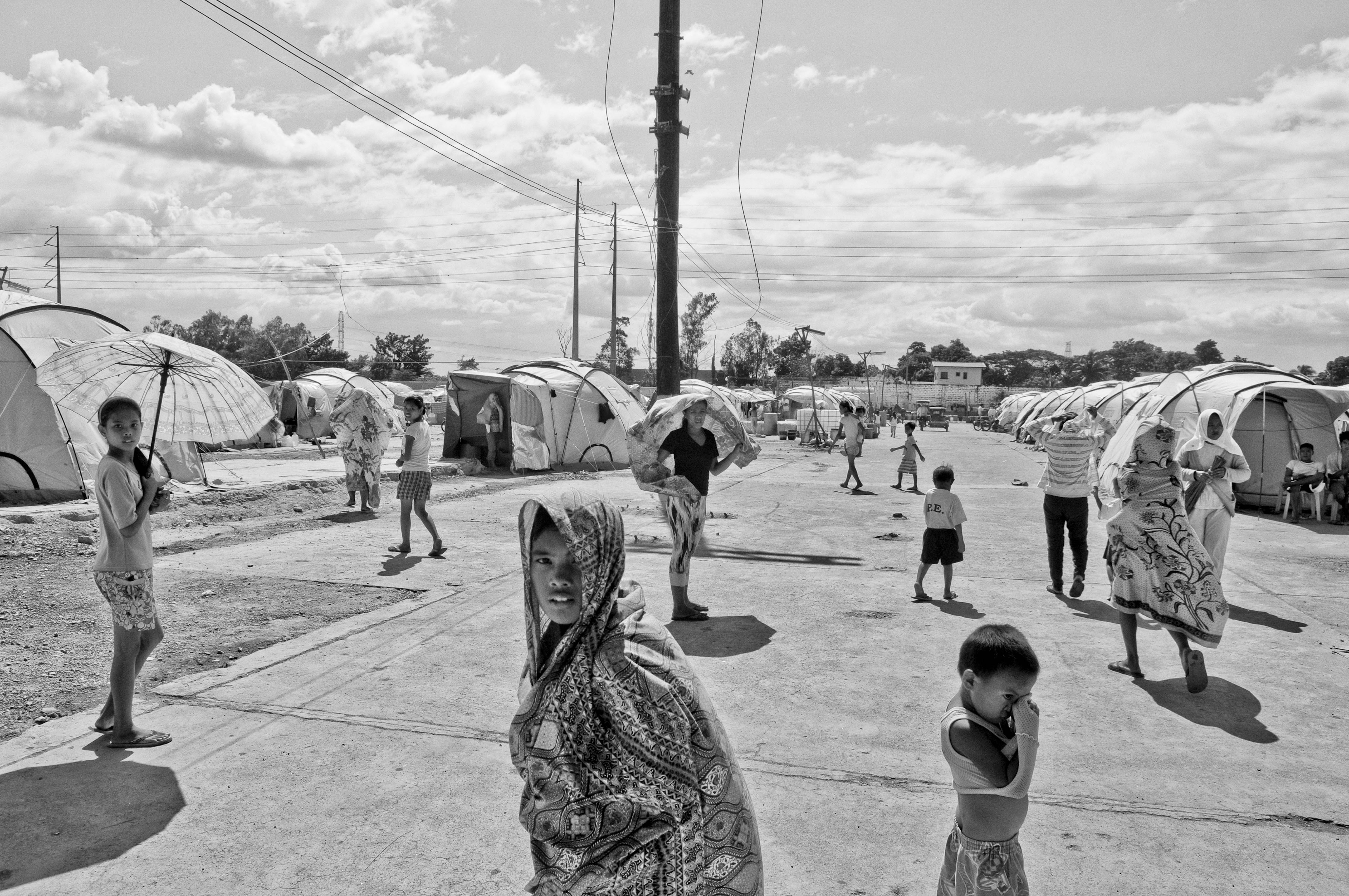Families that have been displaced for several months due to stagnant floodwaters seek temporary shelter in a rundown factory on Oct. 23, 2012 in Laguna, Philippines.