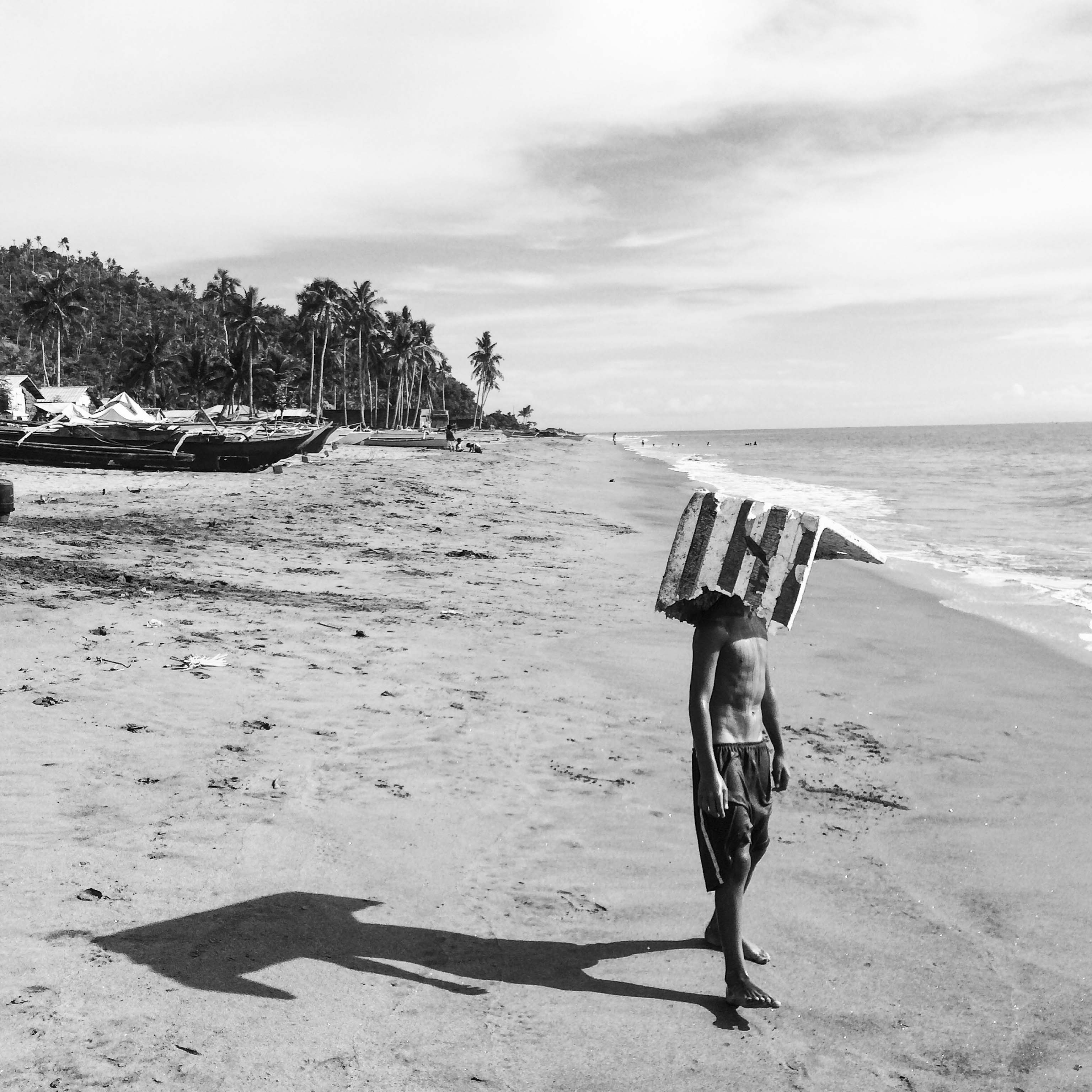 A child takes shelter from the heat with a cardboard panel along the coast of Tanauan on Oct, 7, 2015.