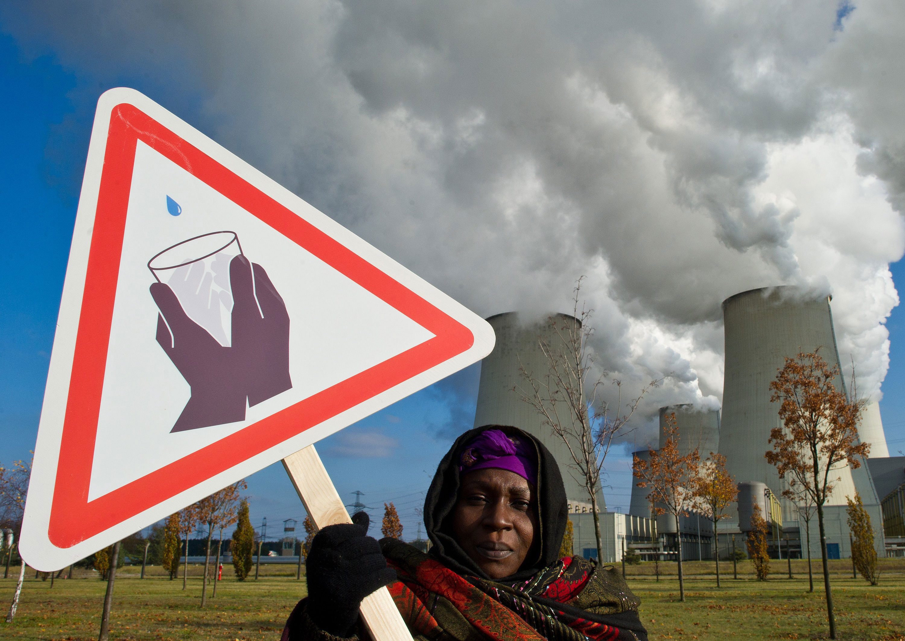 Hauwa Umar-Mustapha from Nigeria, witnesses to climate change, stands with a sign for the shortage of drinking water in front of the cooling towers of the brown coal power plant of Vattenfall AG power company in Jaenschwalde, Germany, Nov. 11, 2011.