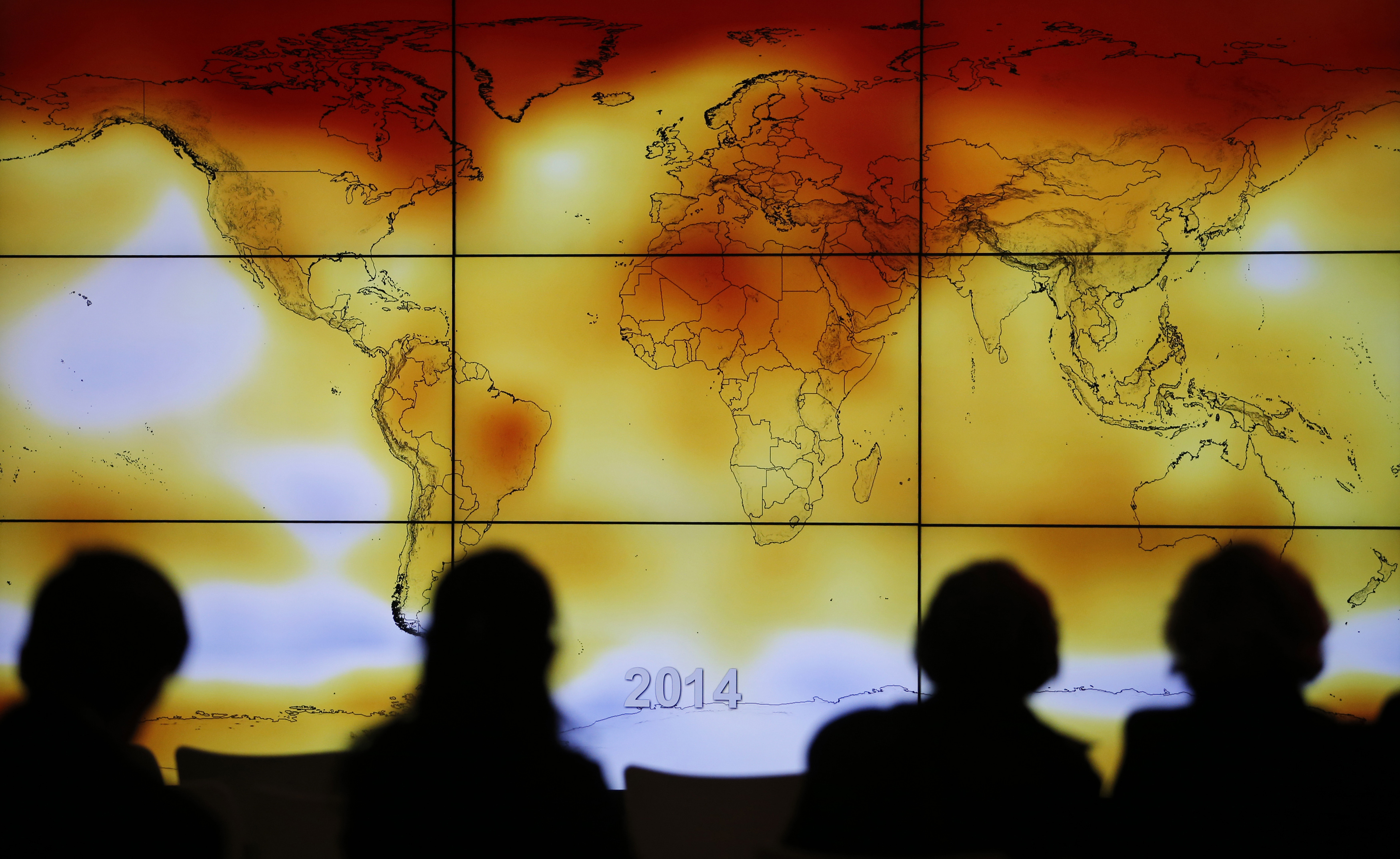 Participants are seen in silhouette as they look at a screen showing a world map with climate anomalies during the World Climate Change Conference 2015 (COP21) at Le Bourget, near Paris, Dec 8, 2015.