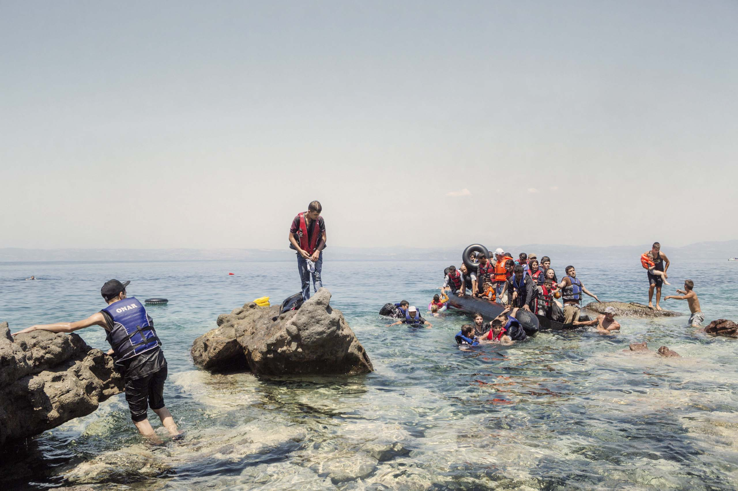 A boat carrying migrants is helped by locals on the Greek island of Lesbos. The boat started to leak, forcing the passengers to swim ashore, Aug. 5, 2015.