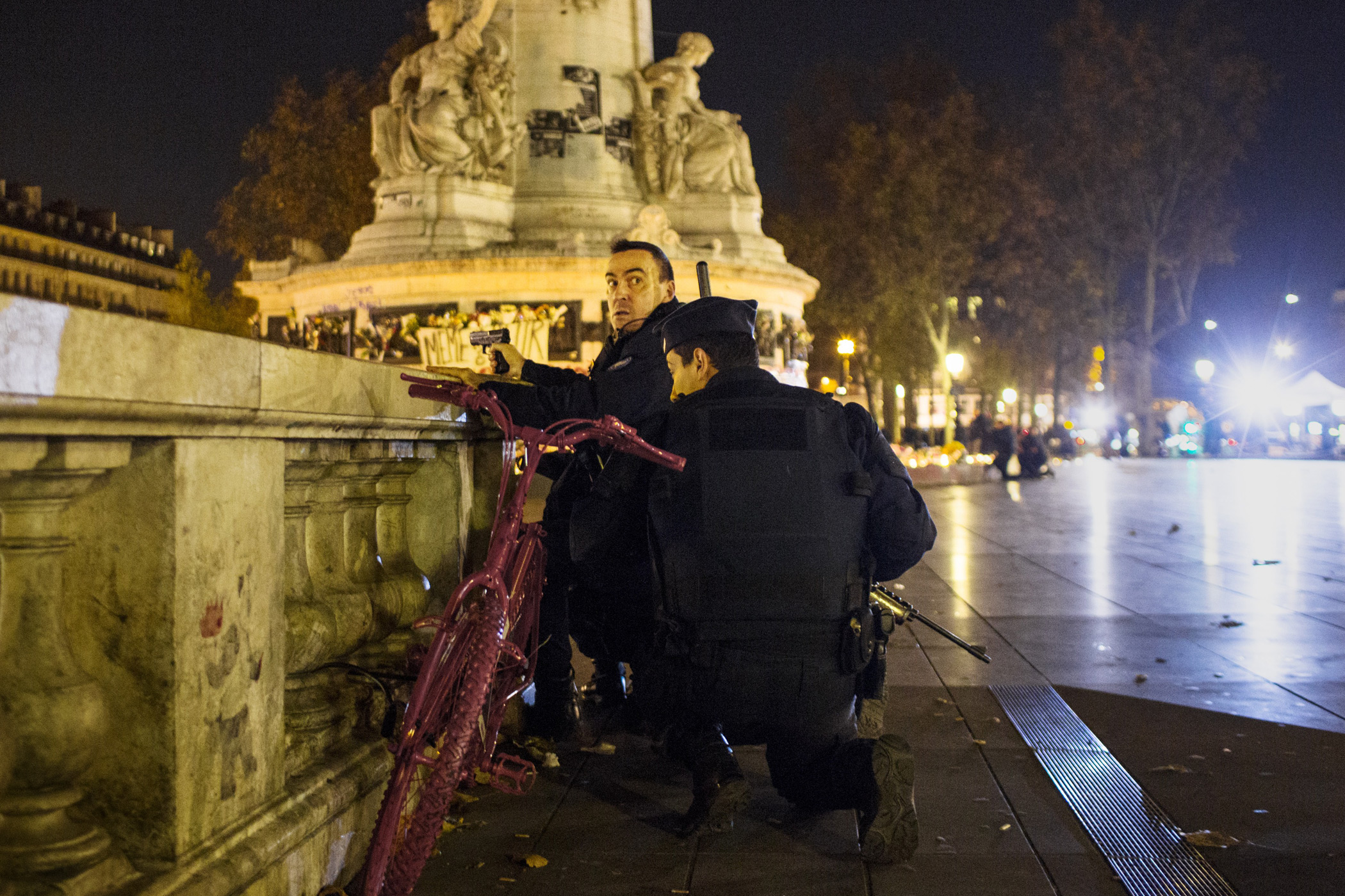 Armed police take aim in Paris' Place de la République during a false alarm on Nov. 15 after terrorist attacks struck the capital city on the night of November 13, 2015. From  See the Heartbreaking Portraits of Parisians in Mourning
