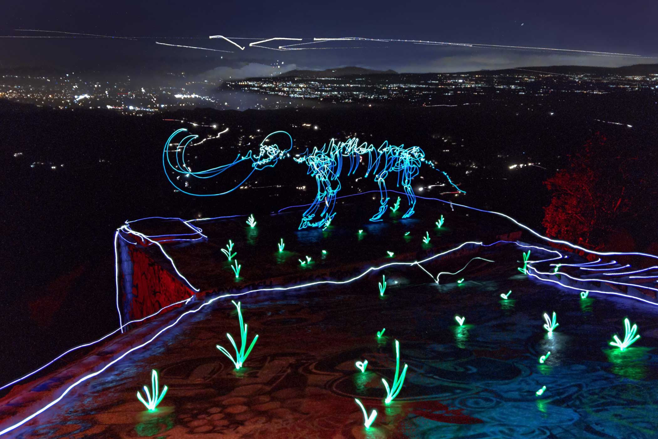 """Darren Pearson lights up the night with colorful characters and scenes in his LED paintings. For Tree of Light, he """"sketches"""" midair with a handheld light, taking long-exposure photos with the NightCap Pro app on iPhone 6s Plus. His Apple Watch acts as a viewfinder throughout the process, giving him a live preview of his drawing as it takes shape."""