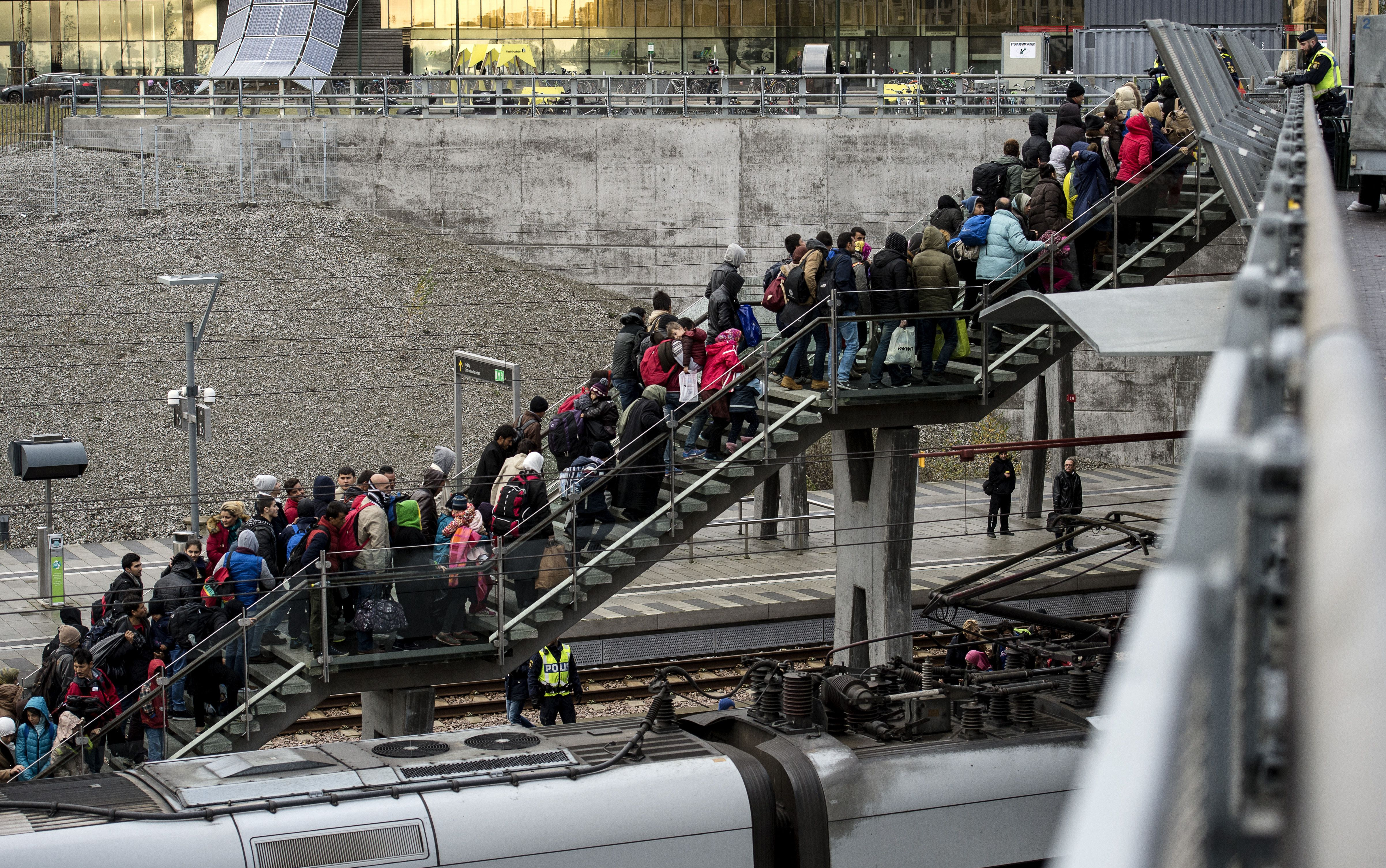 Police organize the line of refugees on the stairway leading up from the trains arriving from Denmark on Nov. 19, 2015