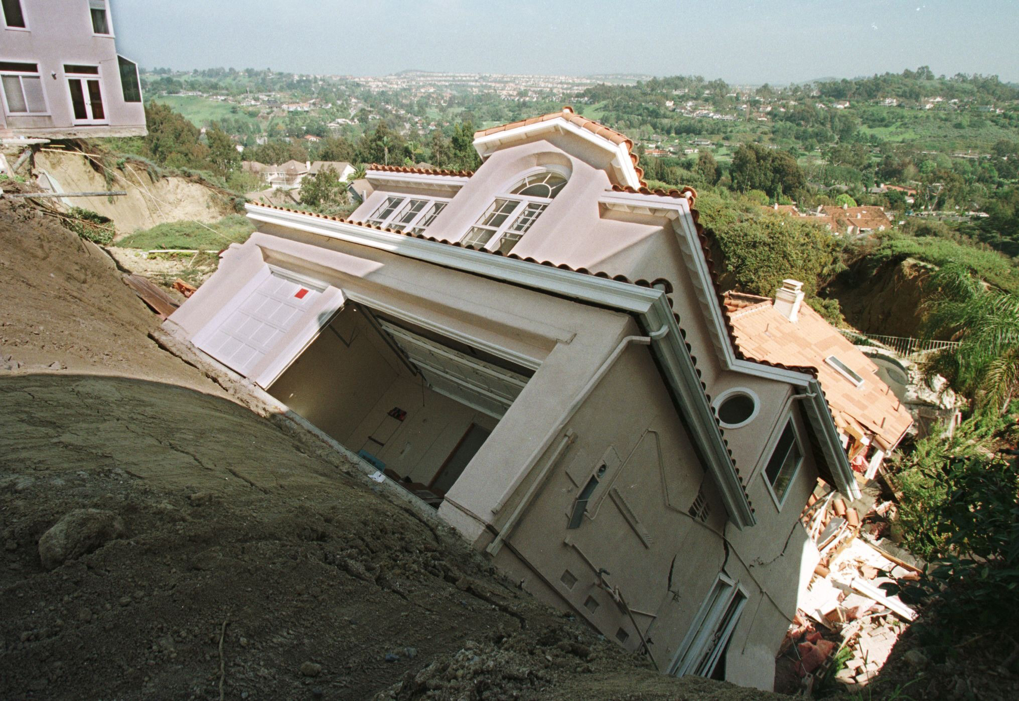 A California home slides down a hill after erosion due to rains tied to El Nino in March, 1998.