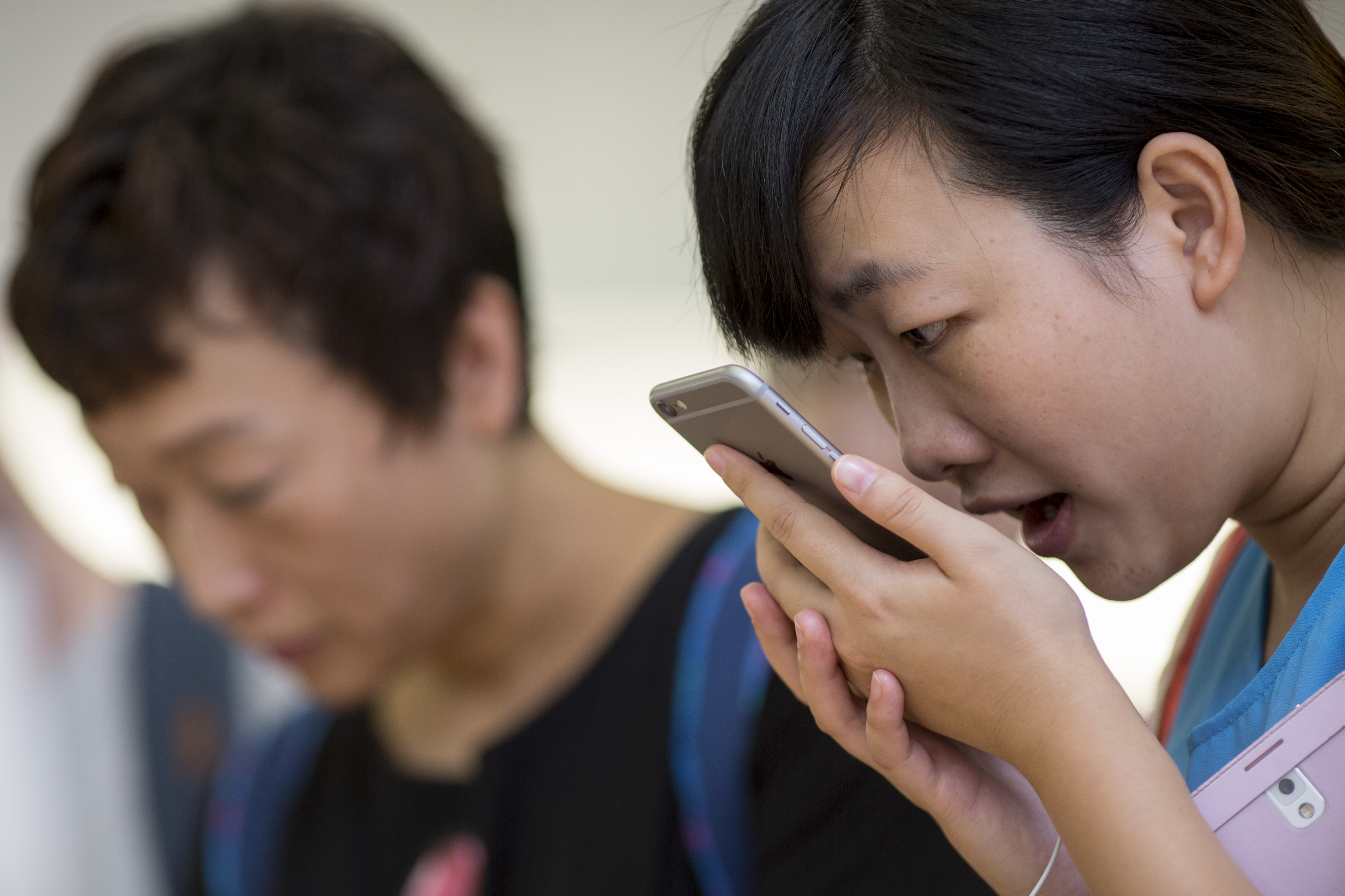 A customer tries the Siri voice recognition function on an Apple Inc. iPhone 6 Plus at the company's Causeway Bay store during the sales launch of the iPhone 6 and iPhone 6 Plus in Hong Kong, China, on Friday, Sept. 19, 2014.
