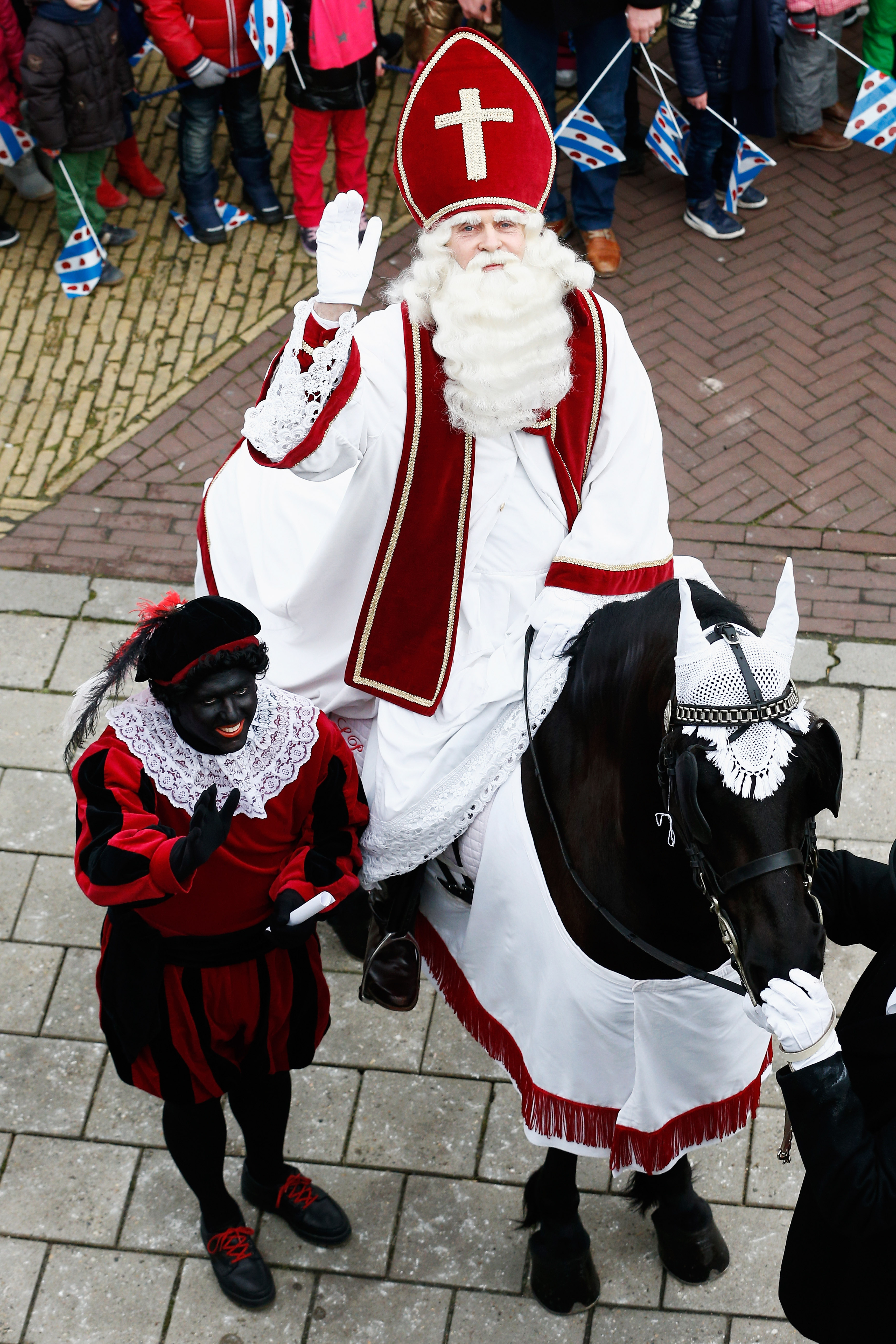 People line the streets near the pier as Sint Piter, named after the patron saint of fishermen Saint Peter, and Zwarte Piet (or Black Pete) arrive on February 14, 2015 in Grou, Netherlands.