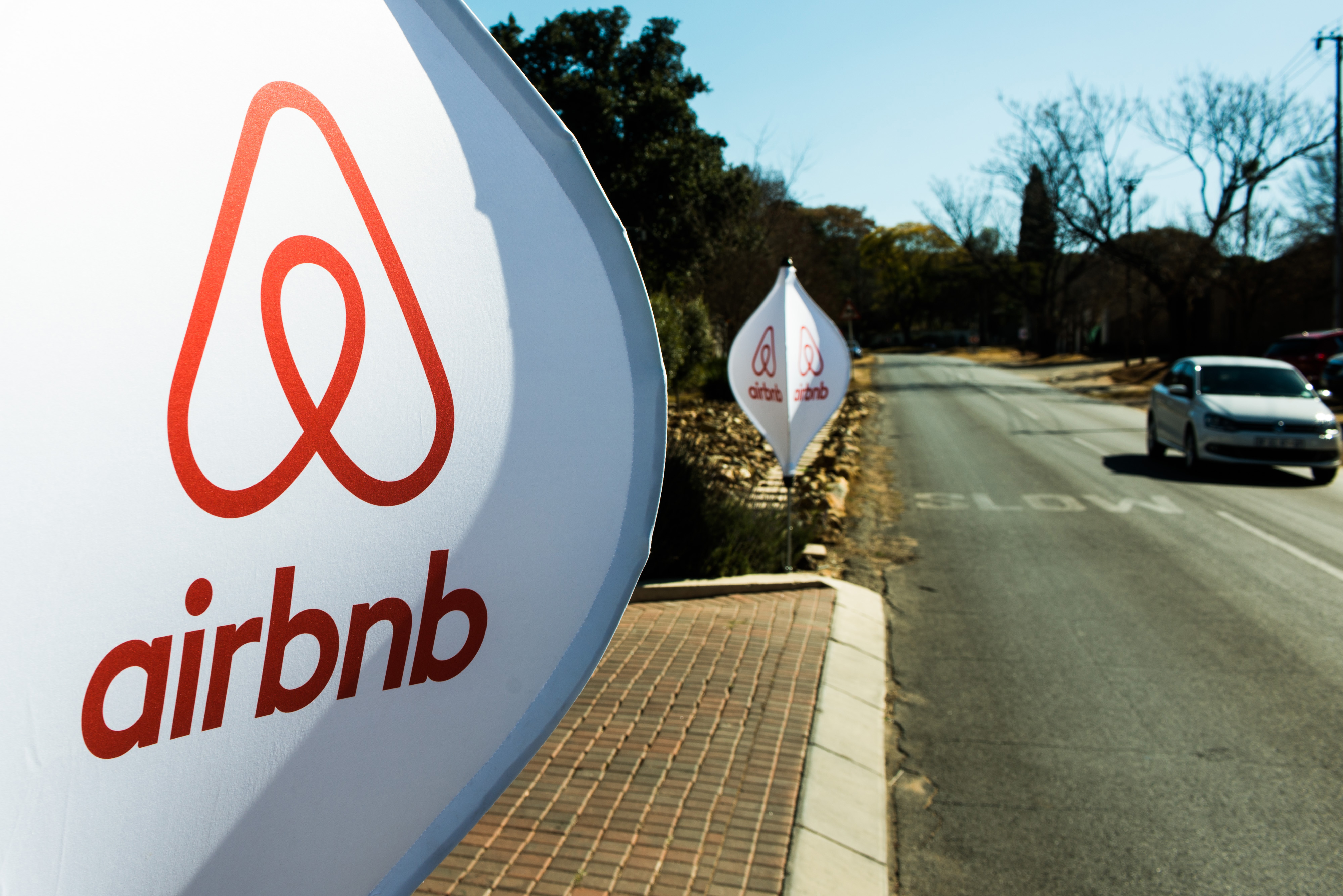 The logos of Airbnb sit on banners displayed outside a media event in Johannesburg on July 27, 2015