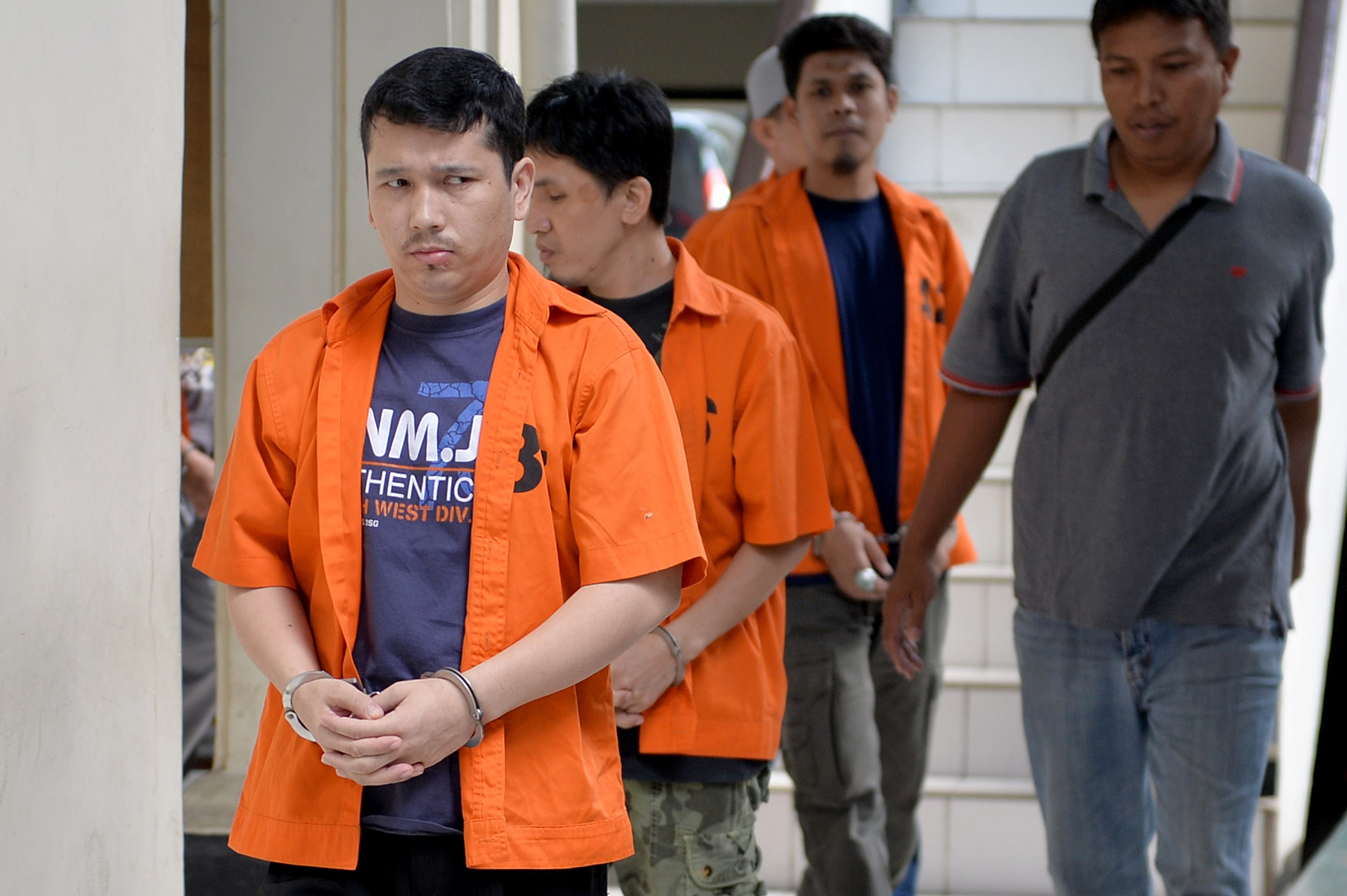 Ahmet Bozoglan, left, a member of China's Uighur minority, walks for his appearance at the North Jakarta District Court on terrorism charges on July 29, 2015, in Jakarta
