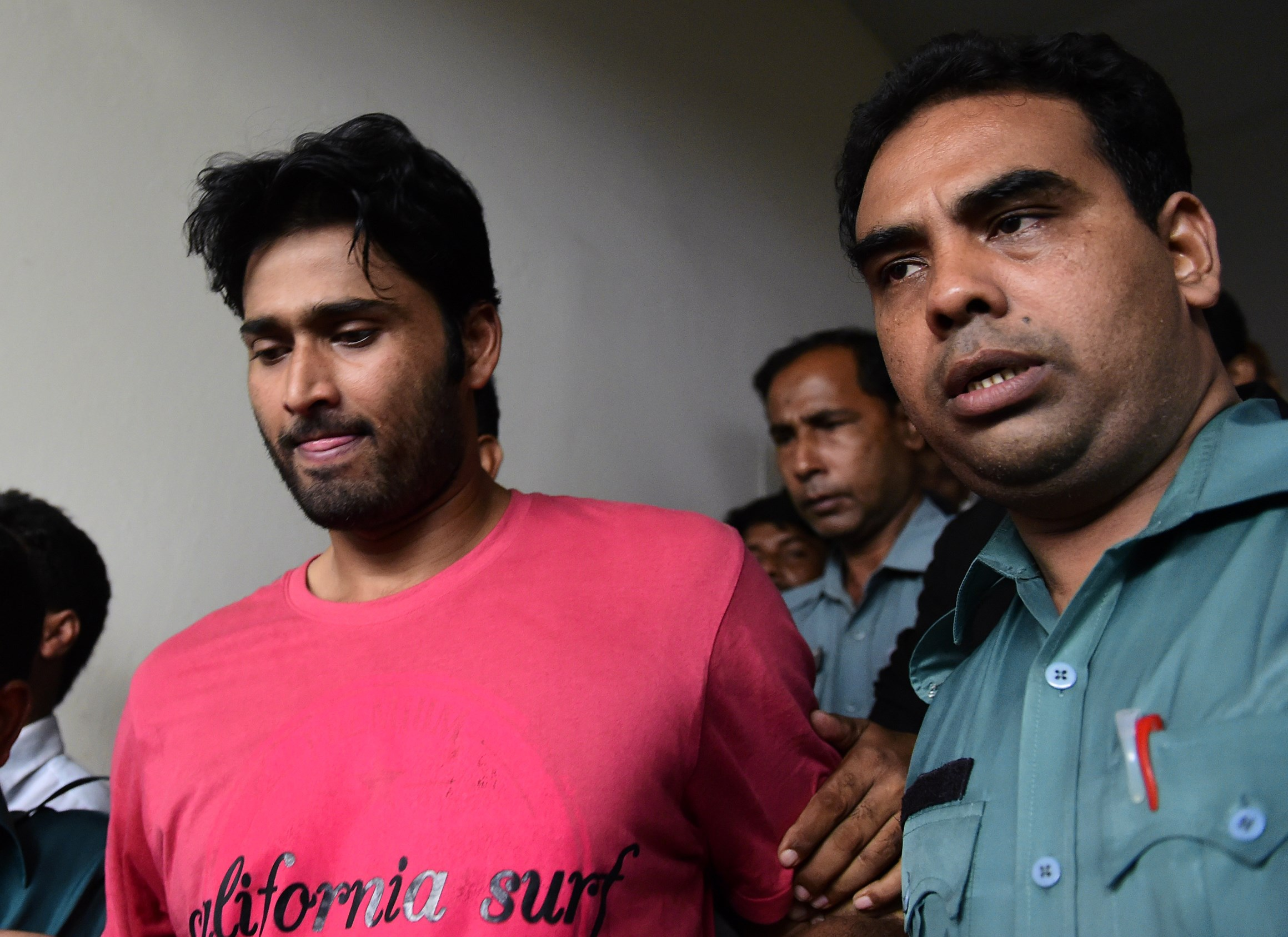 Bangladeshi security personnel escort fugitive cricketer Shahadat Hossain, center, after he surrendered in Dhaka on Oct. 5, 2015