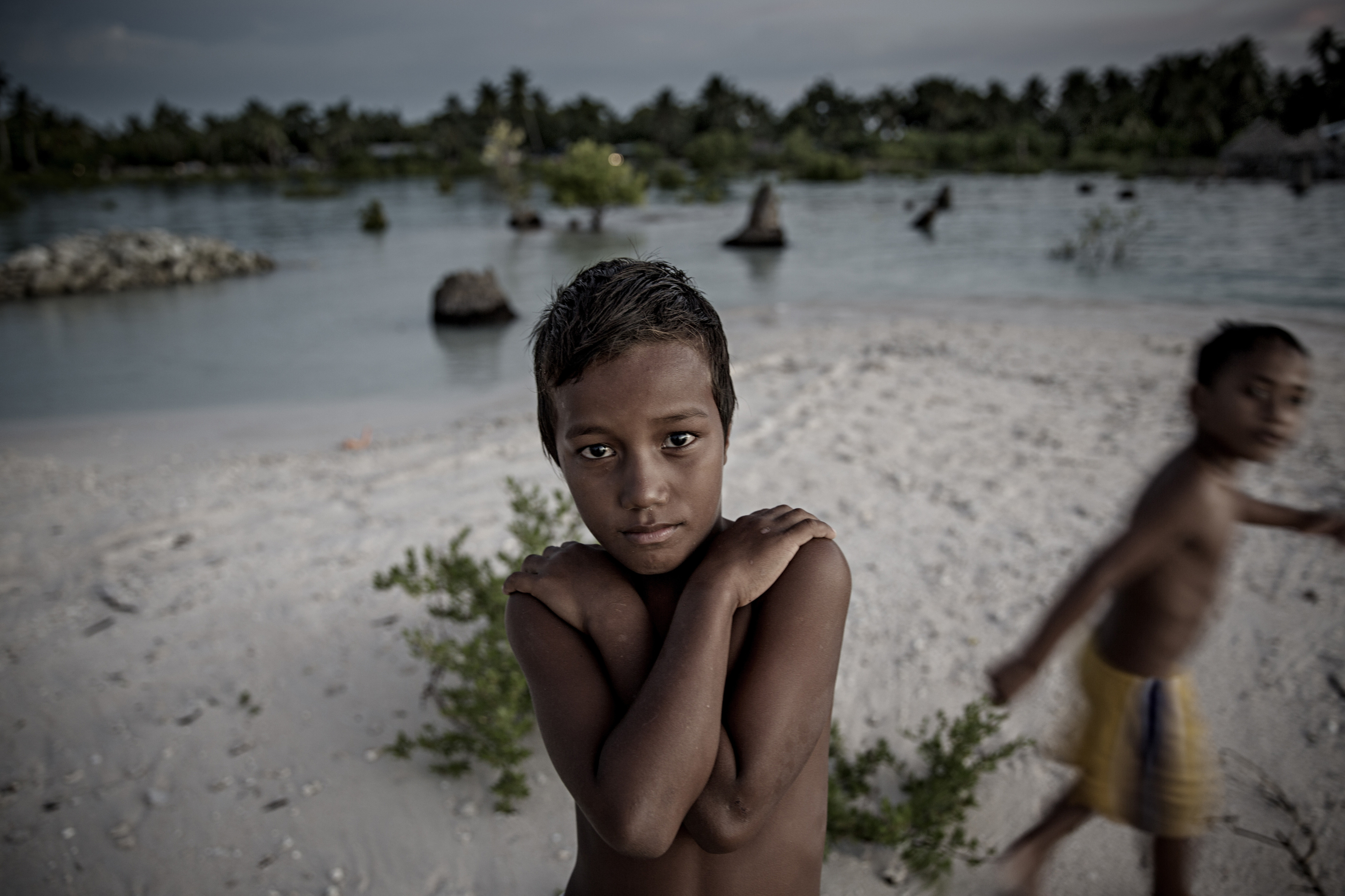 A young boy stands on a narrow strip of land that luckily didn't flood and prevented his home from being drowned in the sea with the village Eita, Kiribati on Sept. 30 2015.