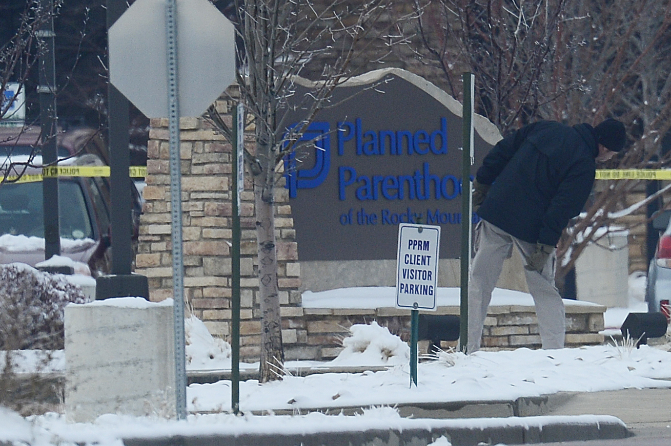 An investigator looks around the front sign of Planned Parenthood at Fillmore Street and Centennial Boulevard on November 29, 2015 in Colorado Springs, Colorado. The investigation moves into its third day after a gunman attacked a Planned Parenthood, killing three and injuring nine.