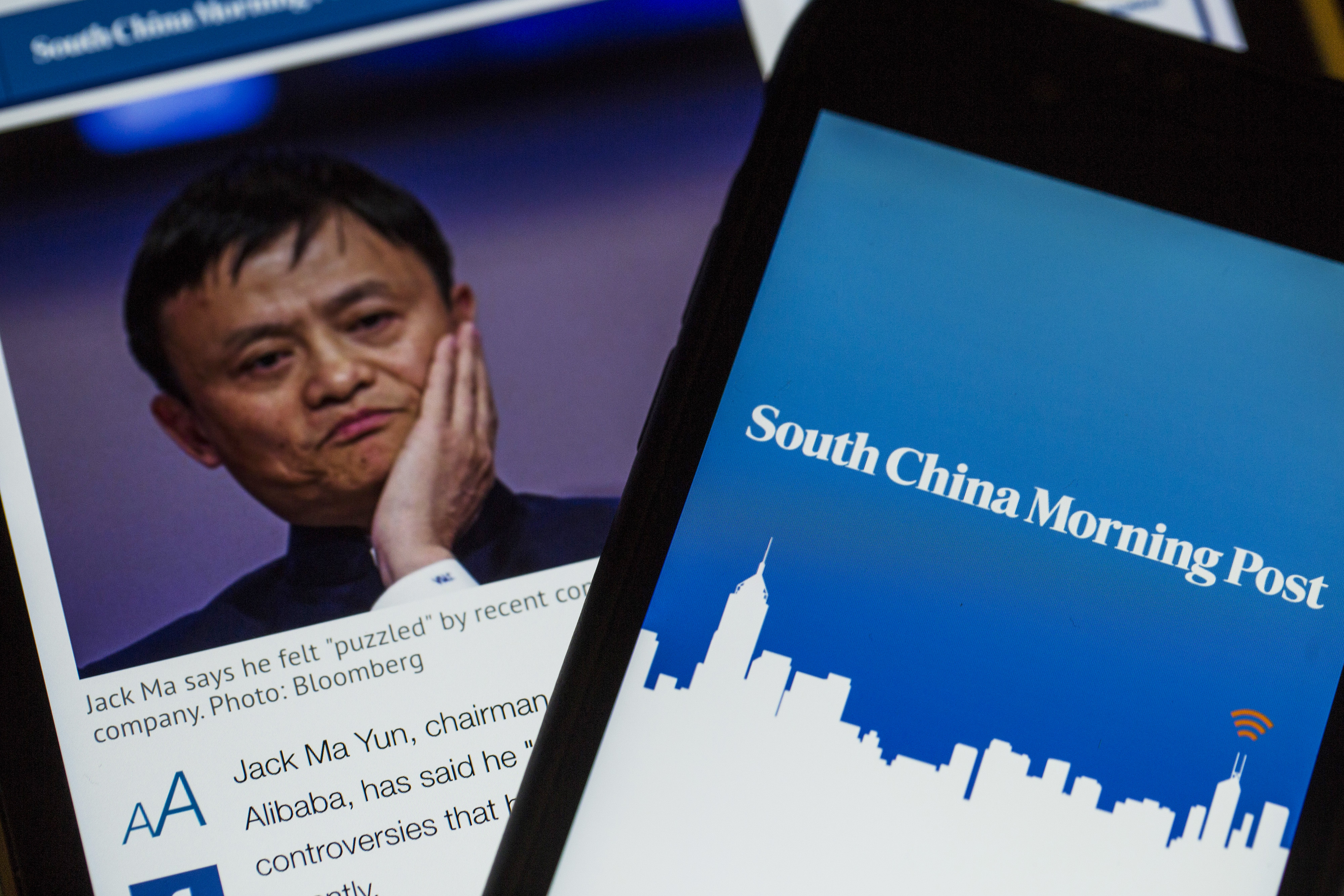 The loading screen for the South China Morning Post (SCMP) app is arranged for a photograph on a smartphone, right, next to a tablet displaying an SCMP article on billionaire Jack Ma, chairman of Alibaba Group Holding Ltd., in Hong Kong, China, on Sunday, Nov. 29, 2015. Ma is in talks to buy a stake in the publisher of Hong Kong's South China Morning Post, according to people familiar with the matter, in what could make him the latest Internet-industry tycoon to pursue the revival of a traditional newspaper.