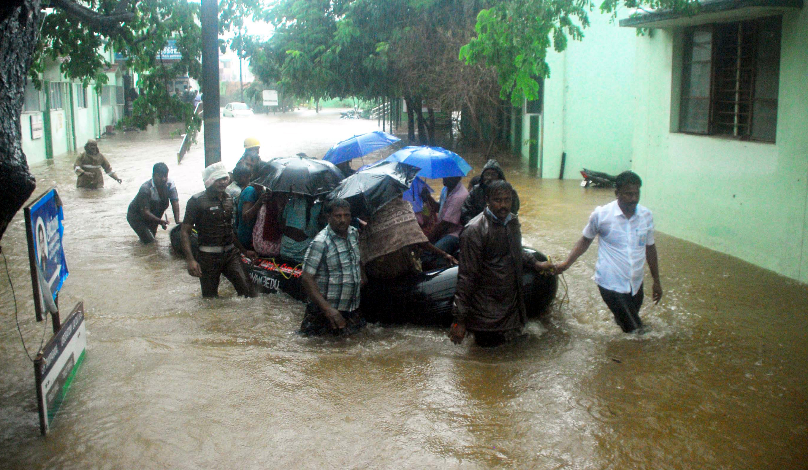 Rescue workers and volunteers use an inflatable boat to take residents through floodwaters in Chennai, India, on Dec. 1, 2015, during a downpour of heavy rain in the southern Indian city