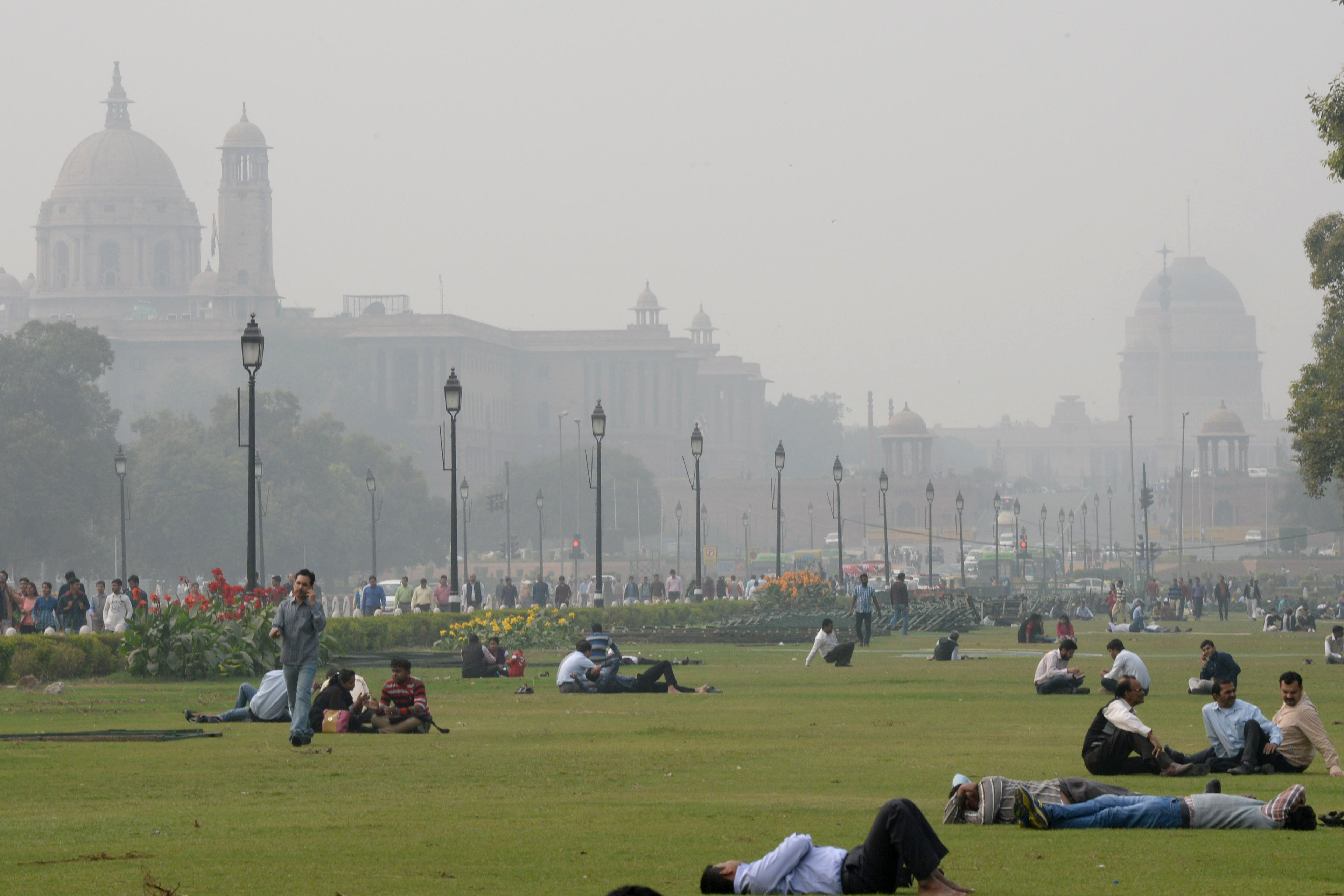 Indian people relax on the lawns near smog enveloped government offices on Rajpath in New Delhi on December 2, 2015.