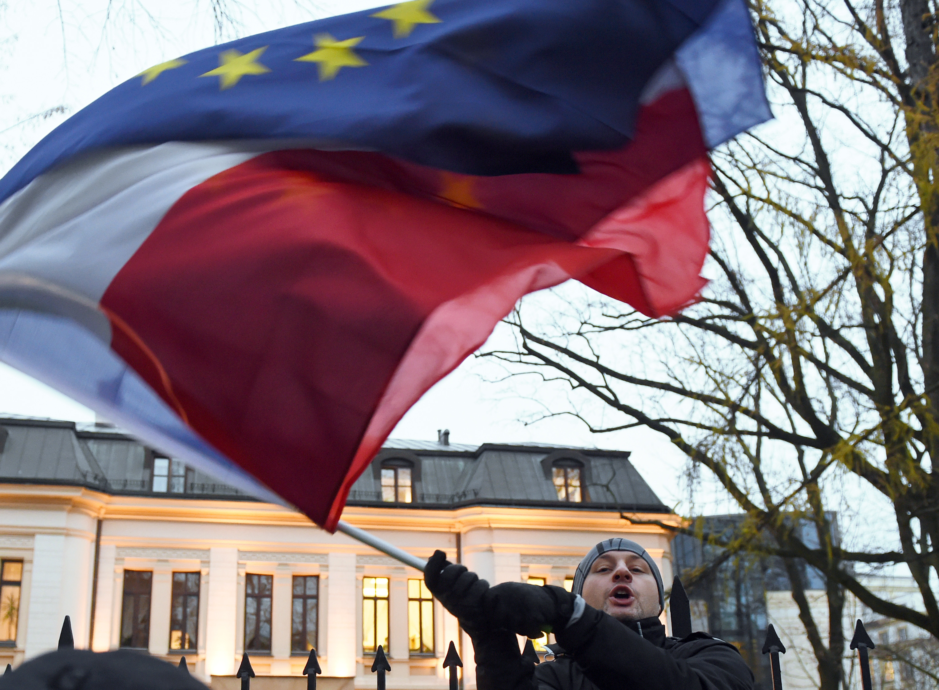 Protester waves flags of Poland and the European Union in front of the Polish Constitutional Court in Warsaw on December 3, 2015.