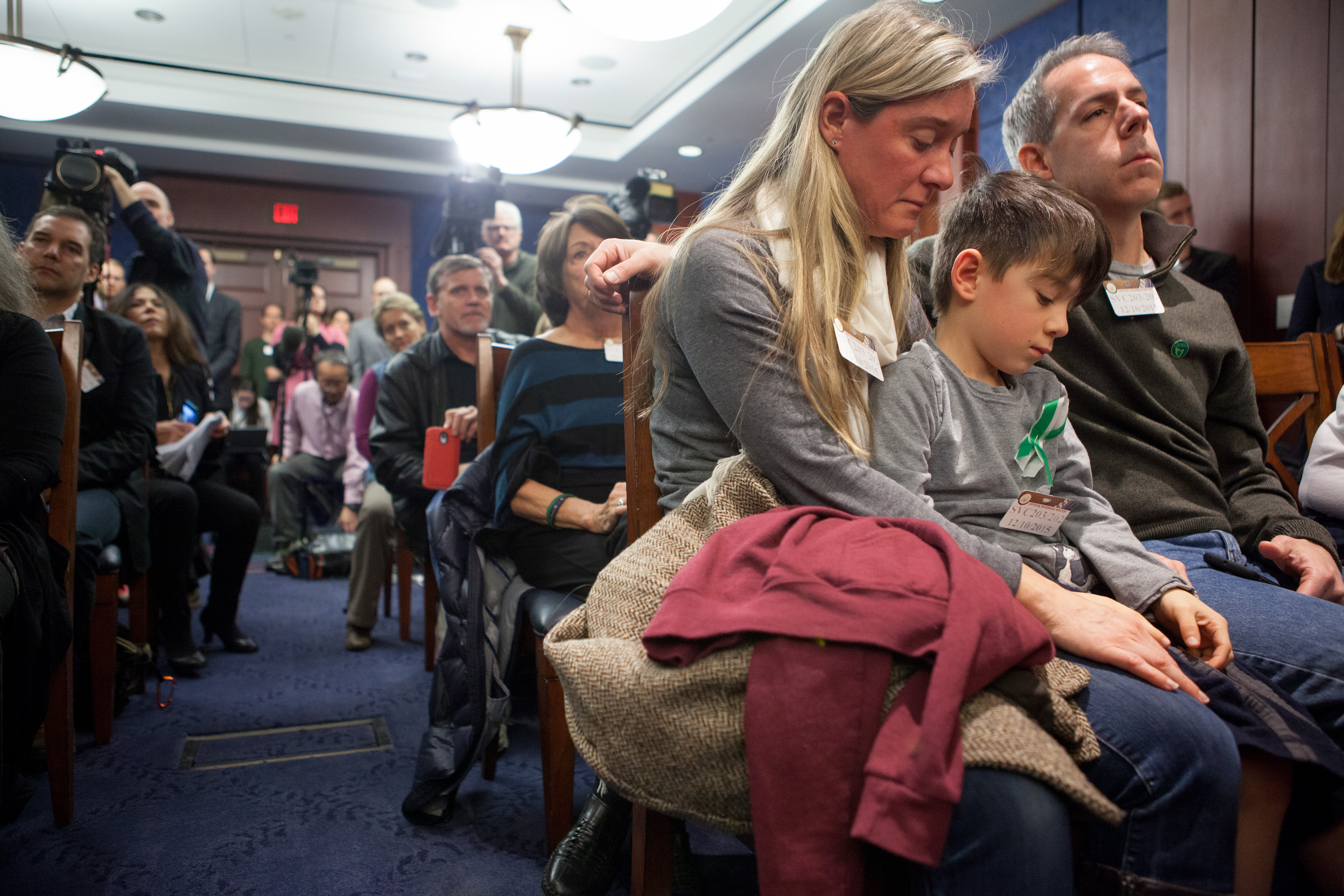Rafe D'Agostino, 7, a second grader, sits between his parents Noelle and Paul D'Agostino during a press conference on Capitol Hill on Dec. 10.
