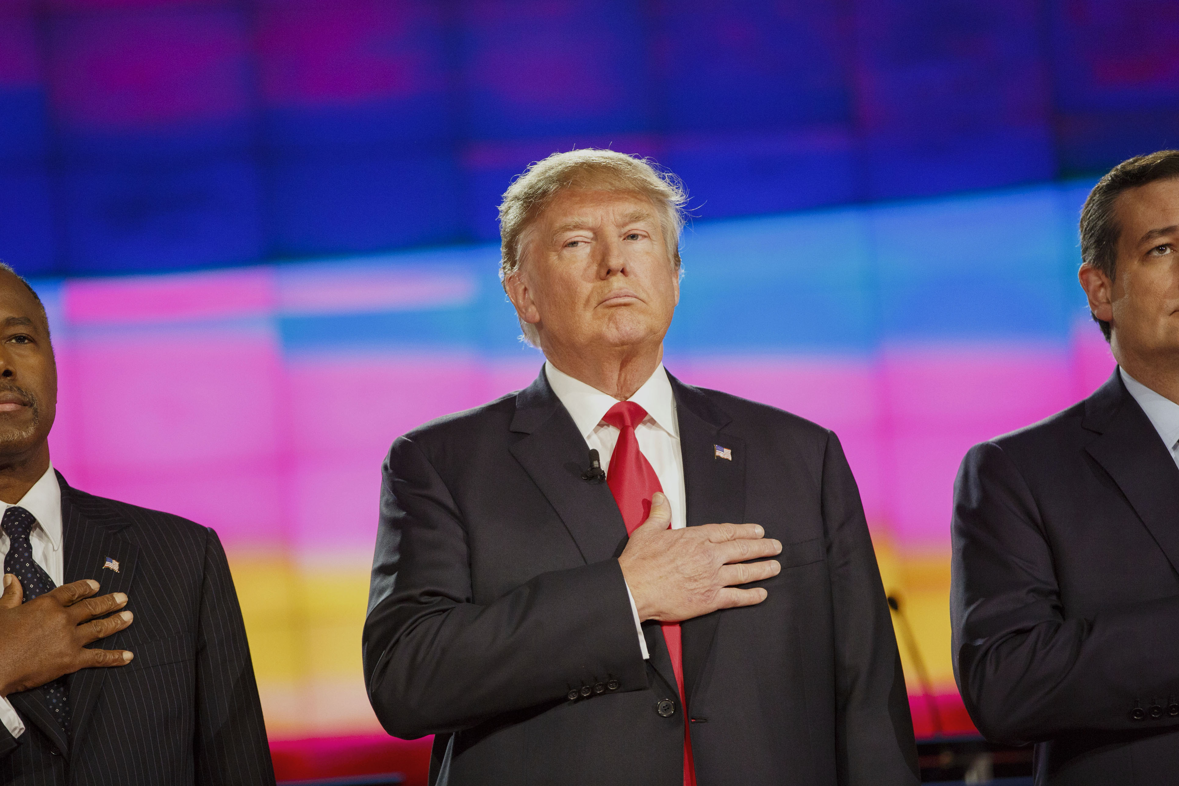Donald Trump, president and chief executive of Trump Organization Inc. and 2016 Republican presidential candidate, center, stands between 2016 Republican presidential candidates Ben Carson, retired neurosurgeon, left, and Senator Ted Cruz, a Republican from Texas, on stage during the pledge of allegiance at the start of the Republican presidential candidate debate at The Venetian in Las Vegas, Nevada, U.S., on Tuesday, Dec. 15, 2015.