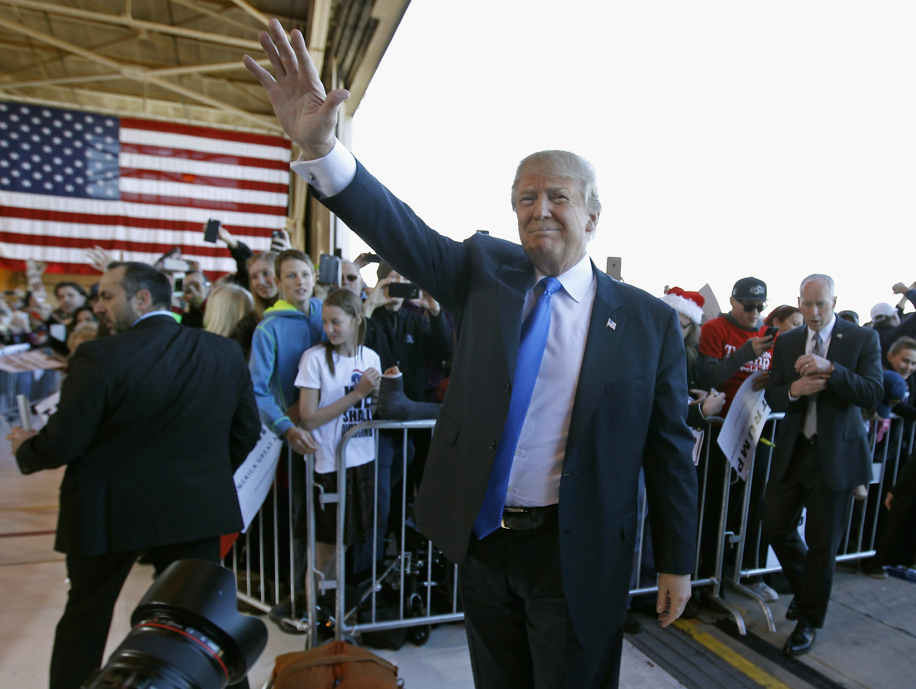 Donald Trump waves to the crowd as he arrives at a campaign event at the International Air Response facility on Dec. 16  in Mesa, Arizona.