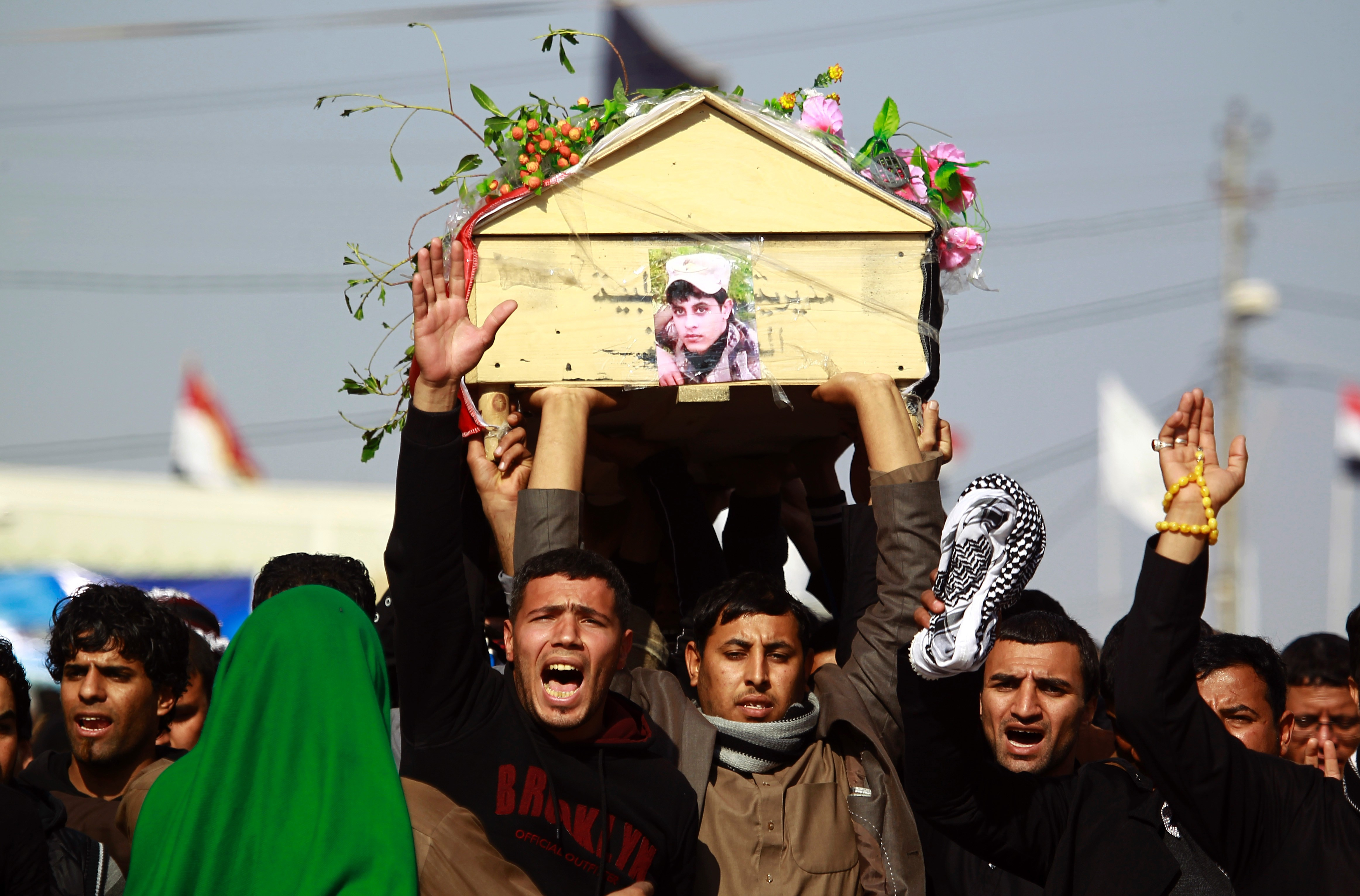 Iraqi mourners carry the body of one of the soldiers who were killed in a so-called friendly fire from a US-led coalition aircraft west of Baghdad, on Dec.19, 2015.