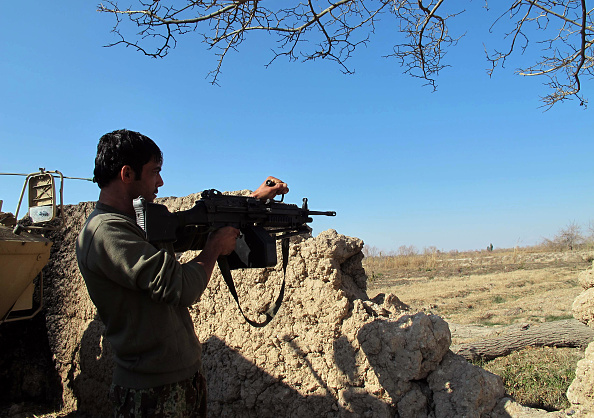 An Afghan National Army soldier keeps watch during a battle with Taliban forces in Helmand province Tuesday.
