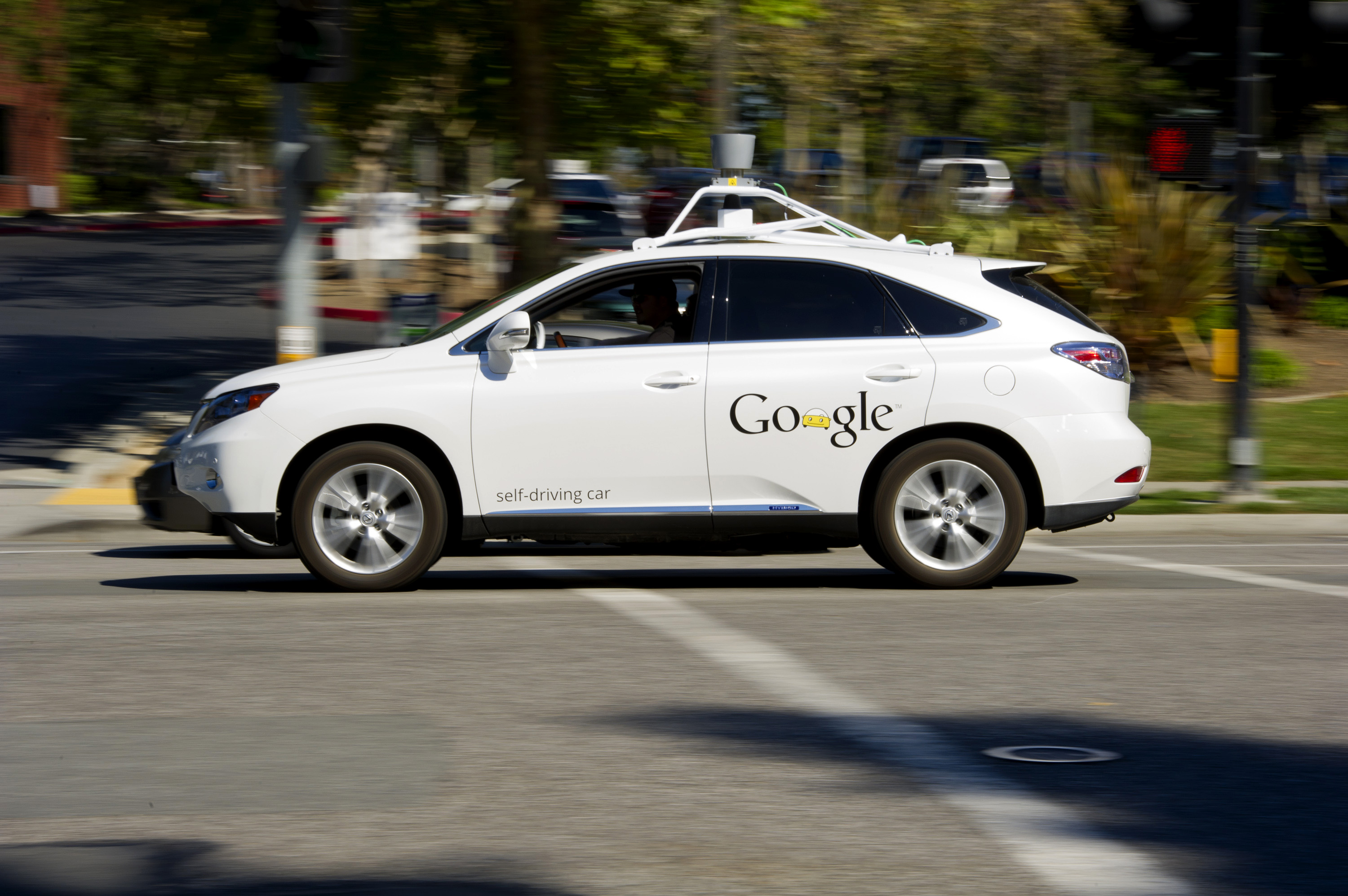 A man drives a Google Inc. self-driving car in front of the company's headquarters in Mountain View, California, U.S.
