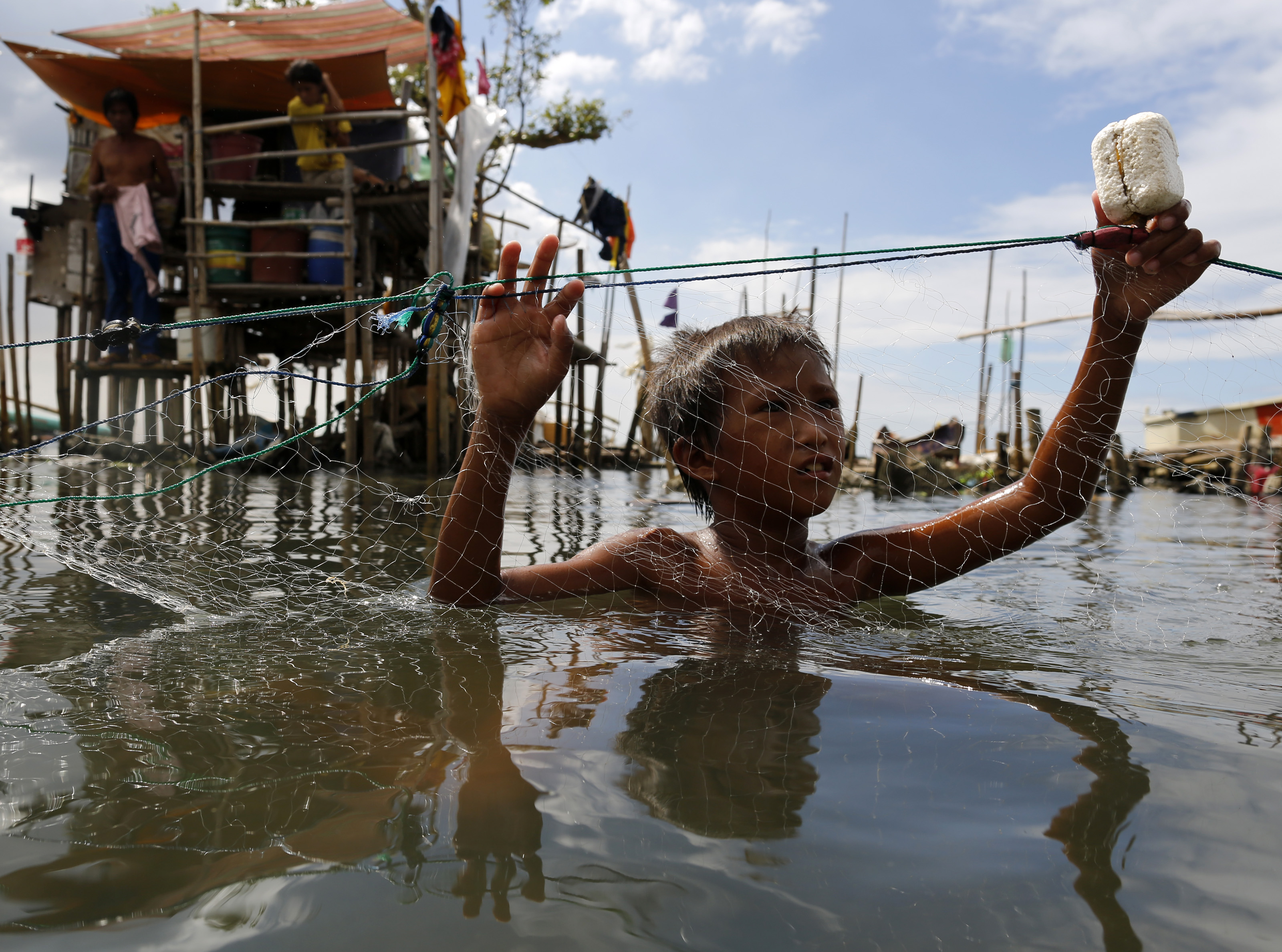 A Filipino boy holds a fishing net at a coastal village in Malabon city, east of Manila, Philippines, 13 December 2015