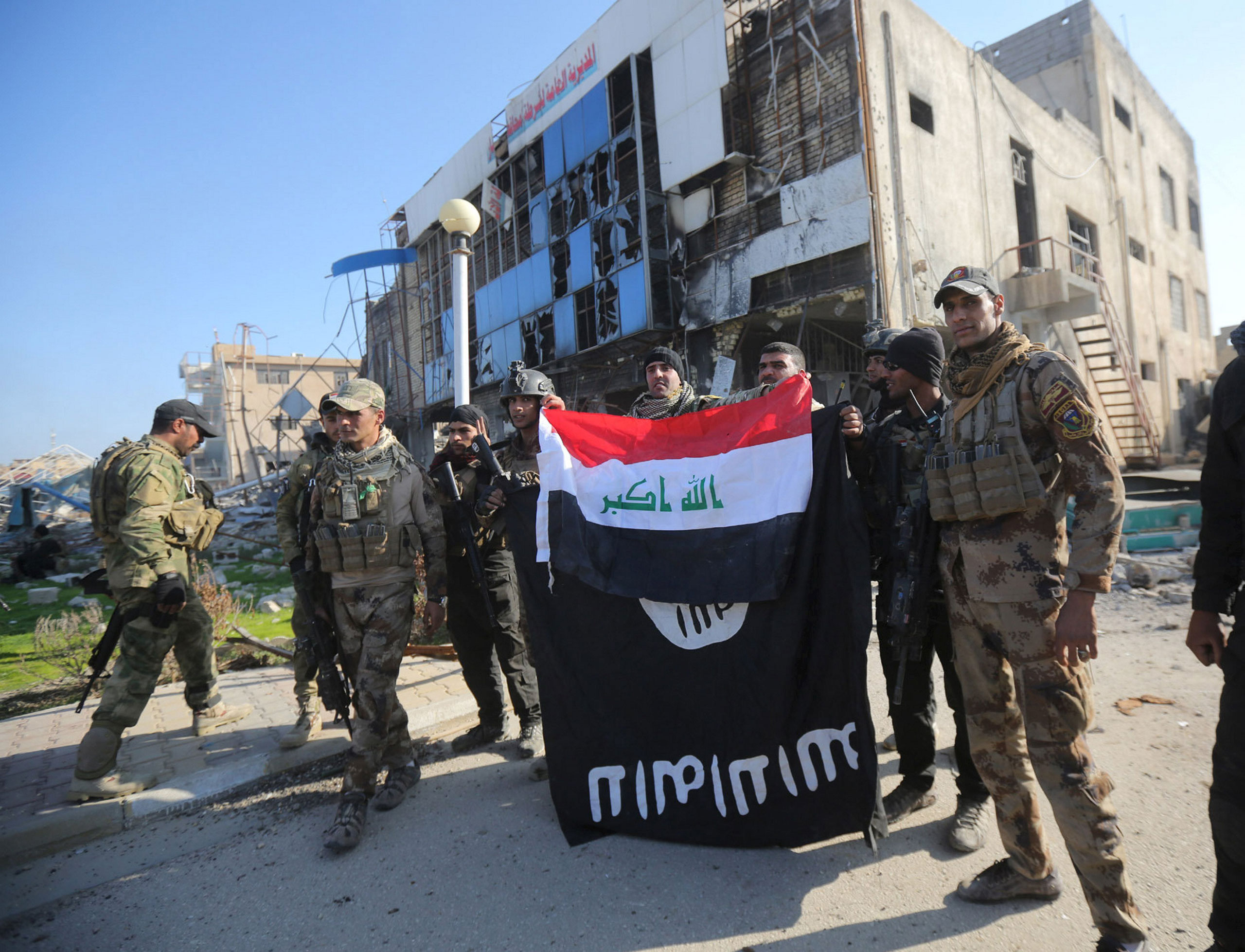 Members of the Iraqi security forces hold an Iraqi flag with an Islamic State flag which they had pulled down at a government complex in the city of Ramadi on Dec. 28, 2015.